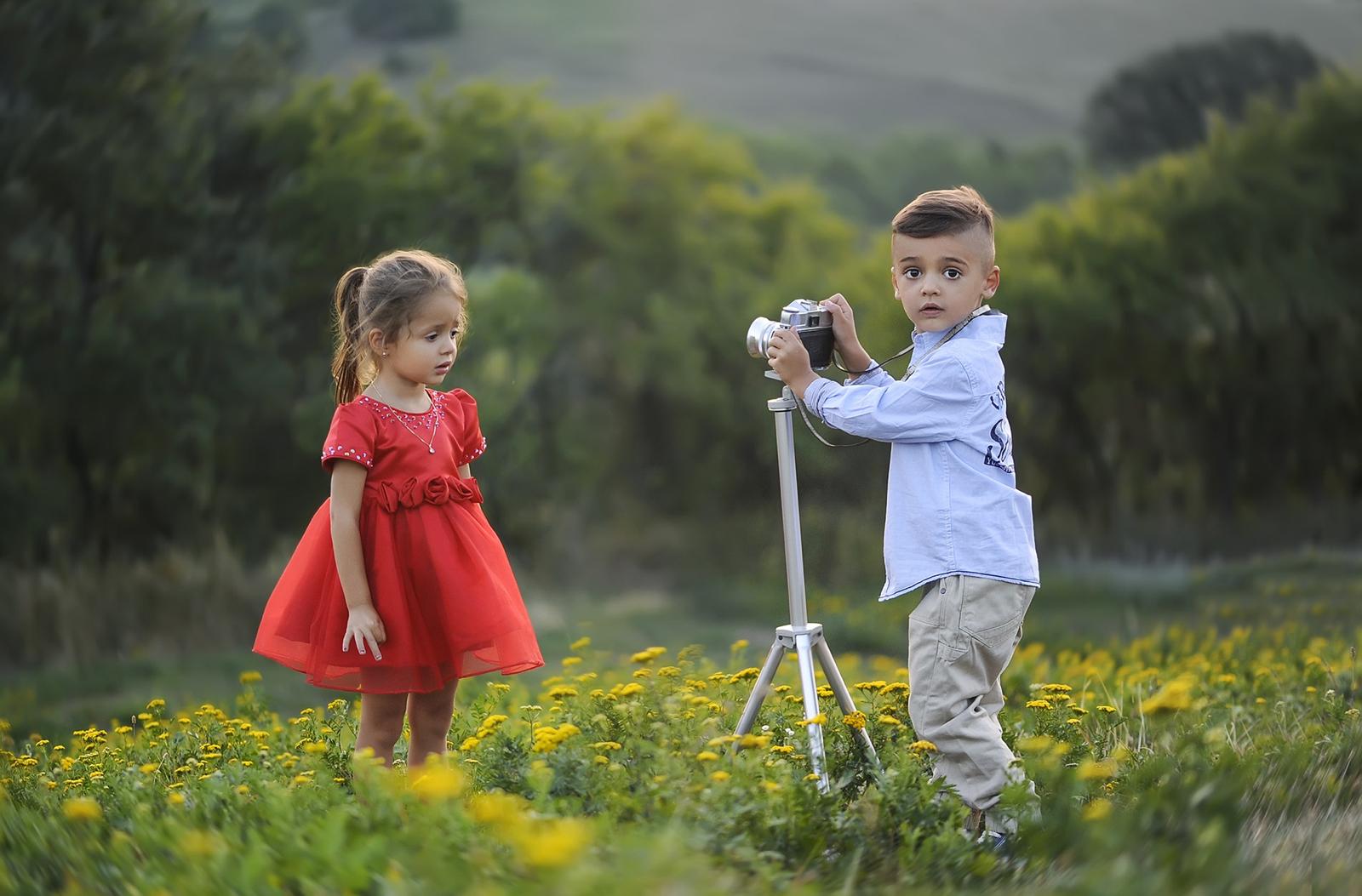 kleine ongen met camera op statief maakt foto van klein meisje in rode jurk op een weide