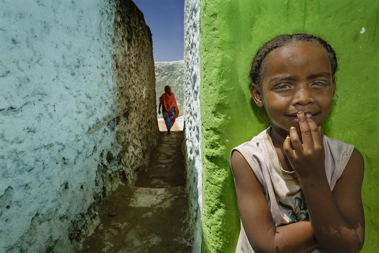 Foto van Stefano Pensotti van een Afrikaans kind naast een doorkijkje, waar een andere vrouw met een rode doek om te zien is verder naar achteren