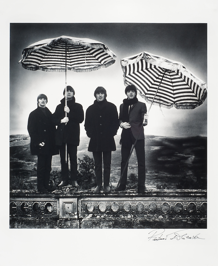 Foto van The Beatles met parasols als paraplu's dragend