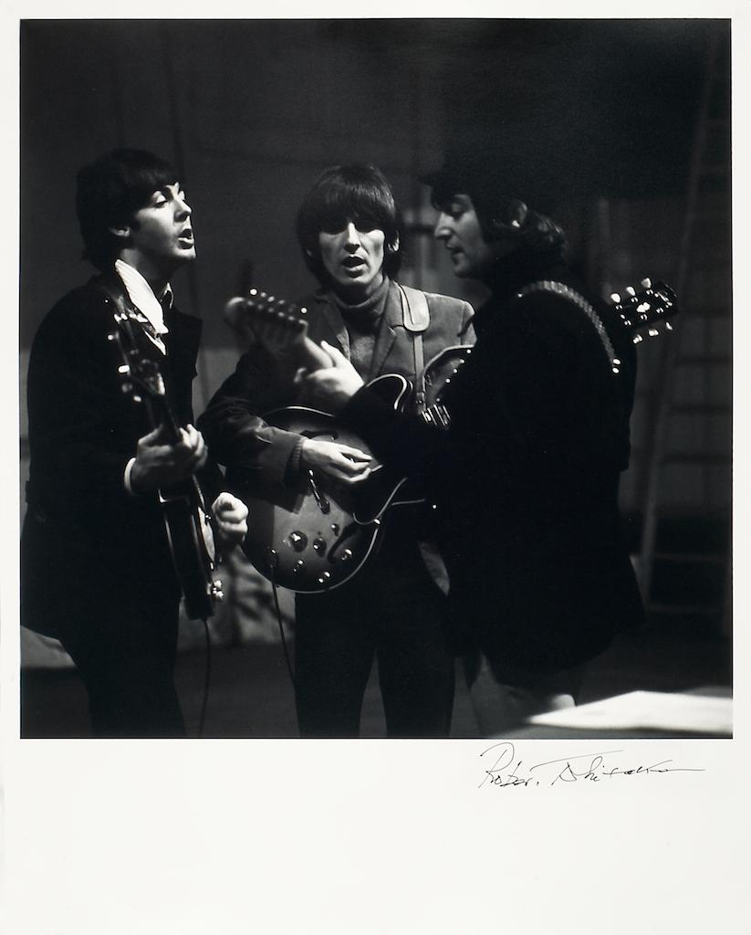 foto van drie van de vier van The Beatles zingend met gitaren