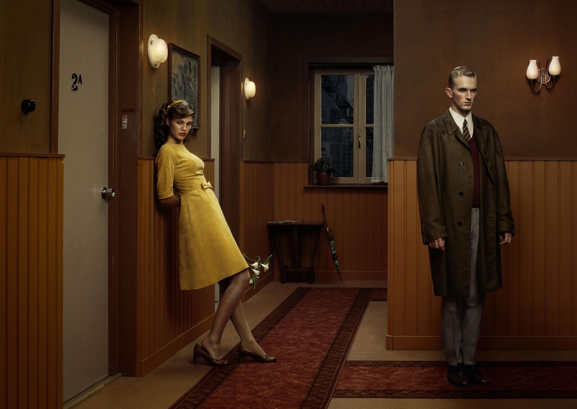 foto van een jonge vrouw en man in de gang van een hotel bij deuren van hotelkamers