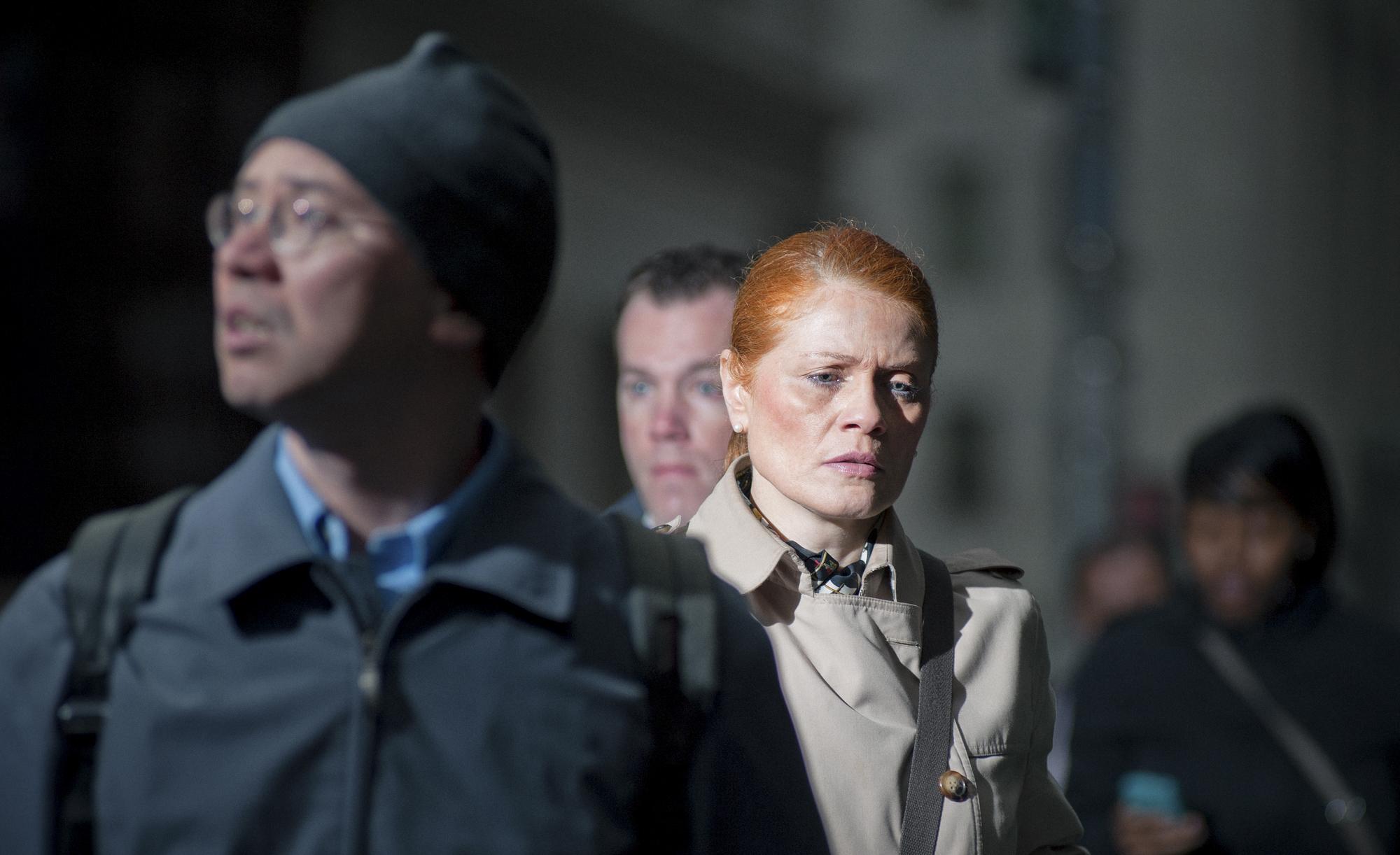 foto van vrouw in close up met rood haar die nadenkend kijkt tussen anderen op straat