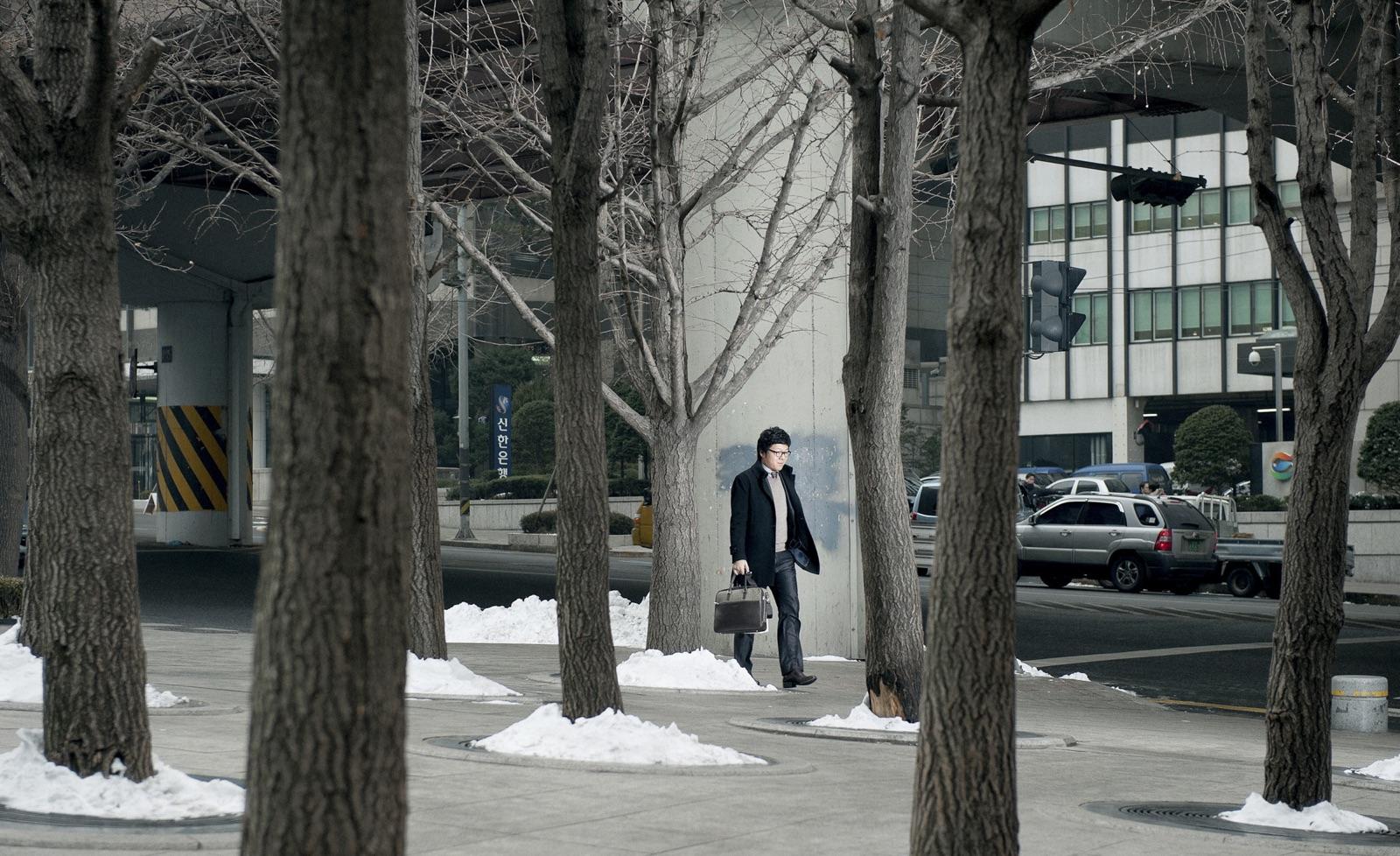 foto van zakenman op straat tussen bomen onder viaduct