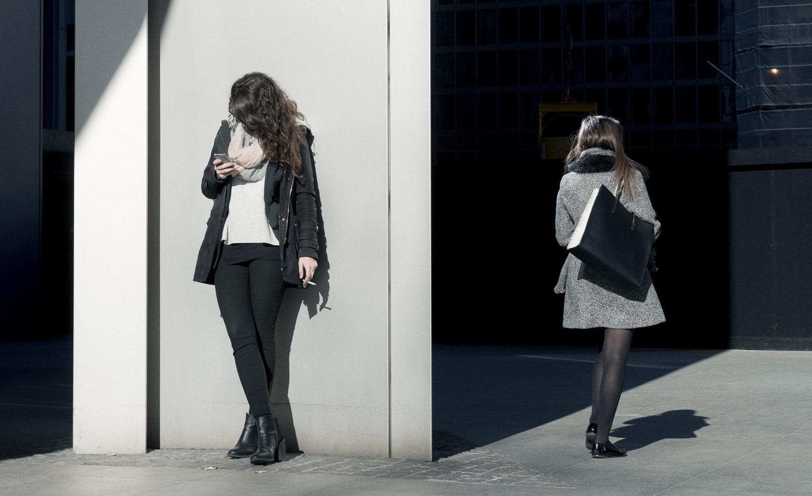 foto van straat met een meisje met sigaret en telefoon tegen gebouw leunend en ander meisje loopt met handtas gebouw in