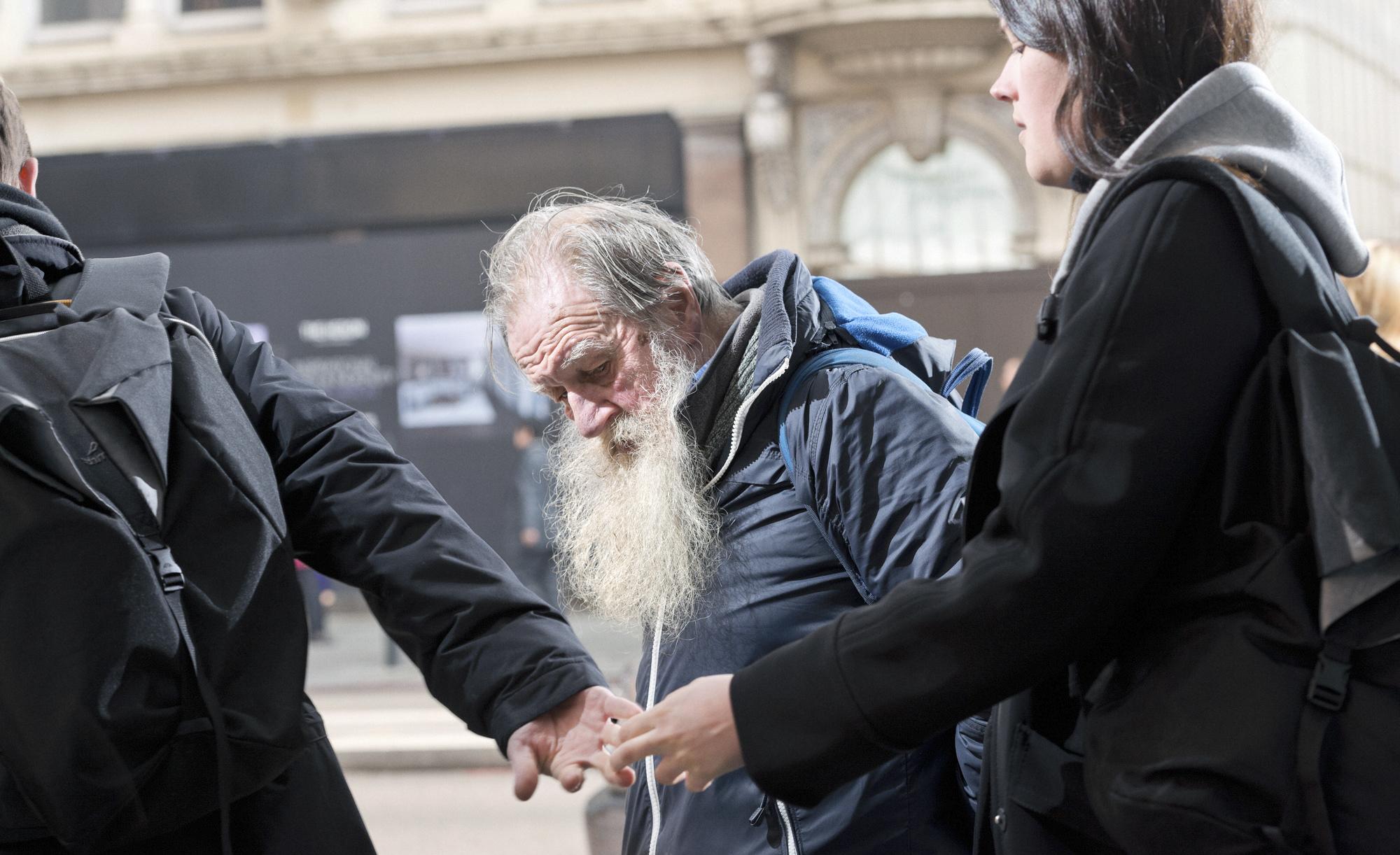 foto van oude man op straat met lange grijze baard kijkend naar de grond terwijl er vlak voor hem twee mensen elkaars hand grijpen