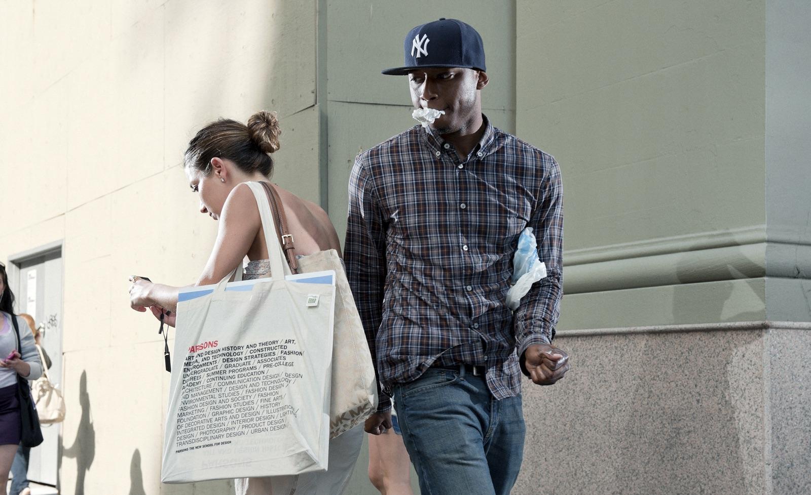 foto van vrouw op straat op telefoon kijkend en man die haar passeert heeft zakdoekje in zijn mond geklemd en kijkt over haar rug met haar mee terwijl hij wel doorloopt
