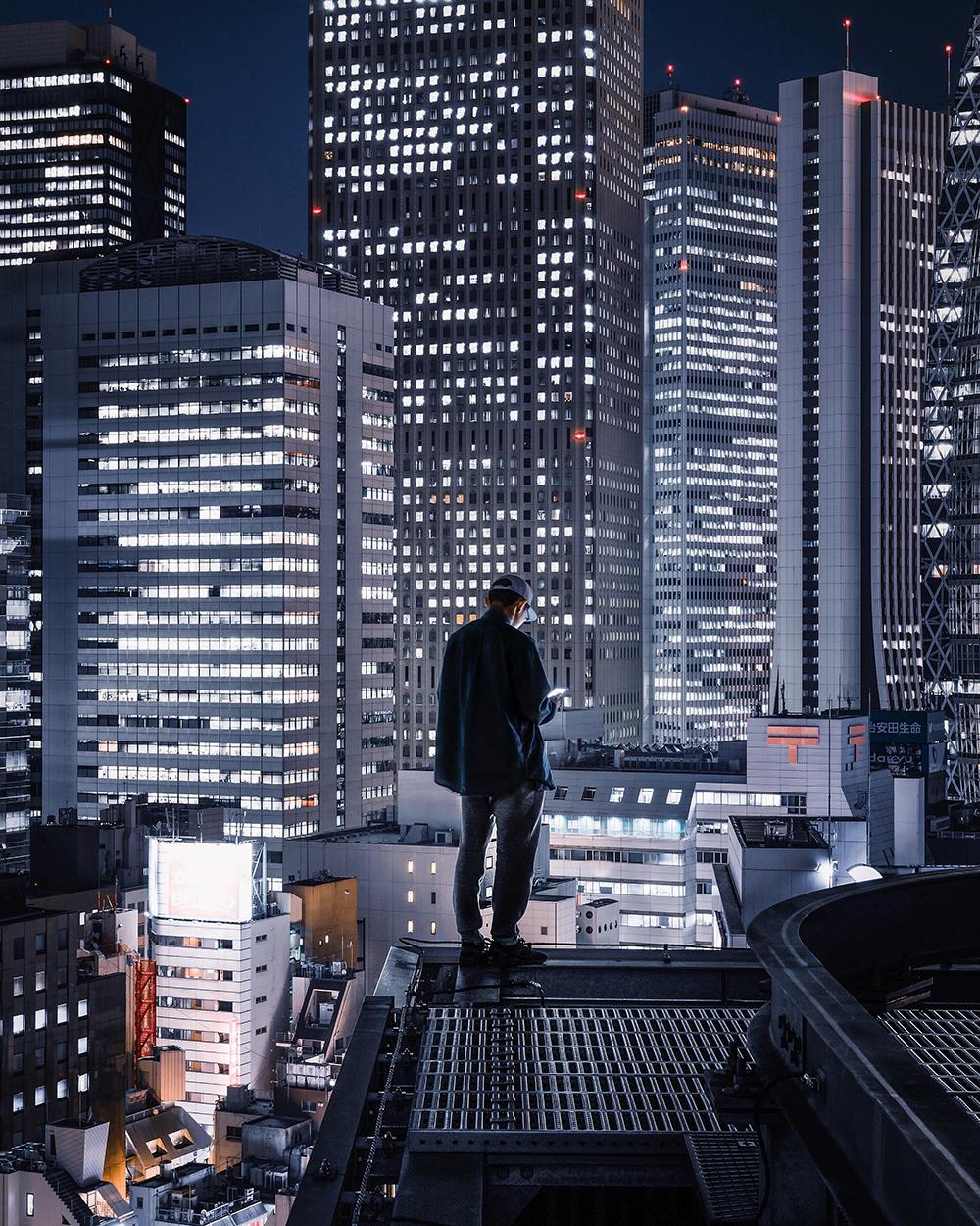 foto van man op dak in stad tussen de hoge gebouwen in de nacht