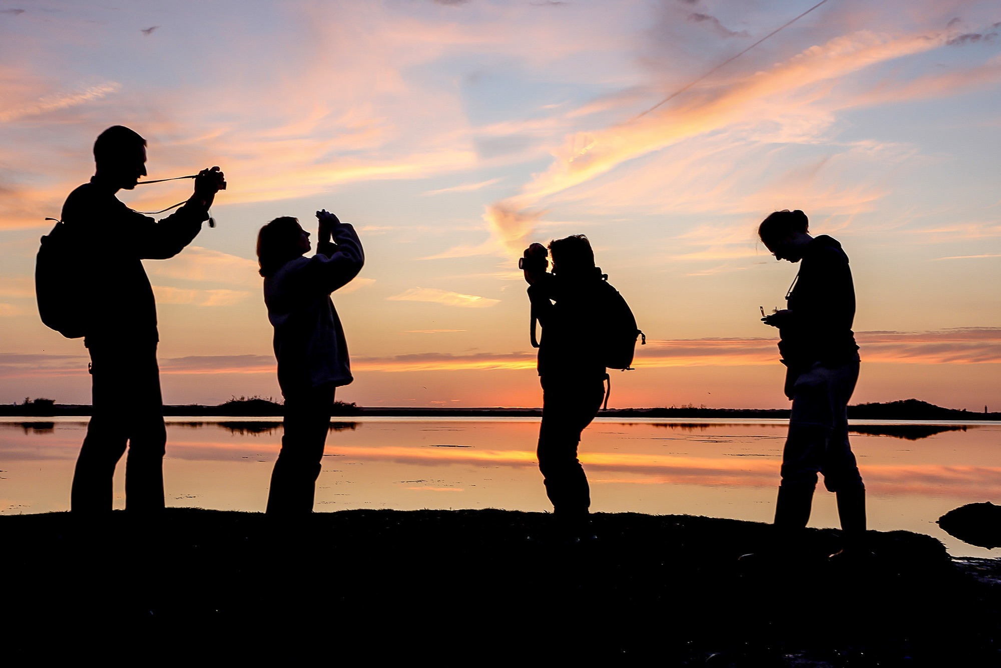 foto van silhouet van vier personen die in de avondzon bij het strand staan te fotograferen