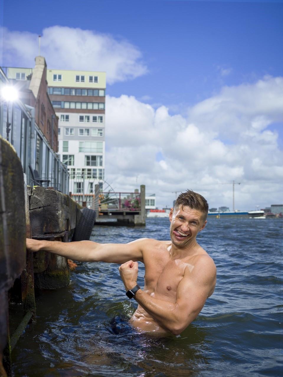 foto van man met ontbloot bovenlijf die zijn tong uitsteekt en een vuist maakt in water bij kade van rivier