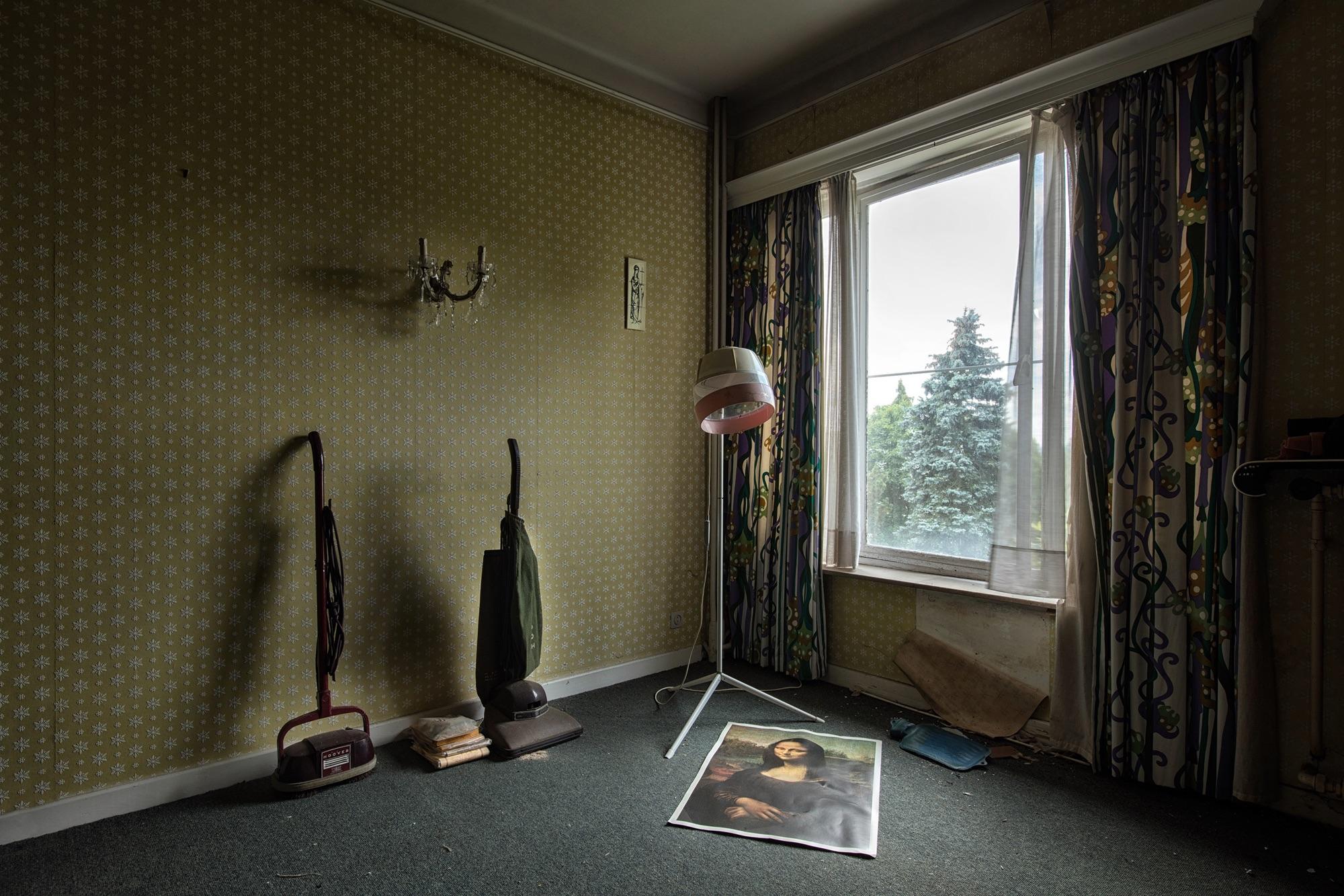 foto van een bruin getinte kamer met een raam en afgebladderd behang waarin een ouderwetse haardroogkap en op de grond een poster van de mona lisa en wat staande stofzuigers