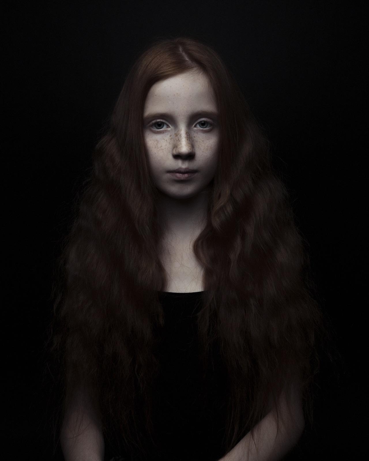portret van jong meisje met rood haar als een mona lisa in een zwarte achtergfrond