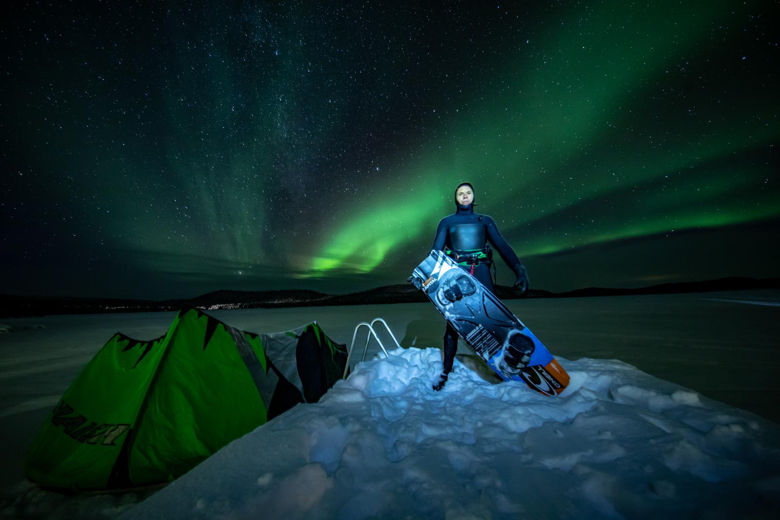 foto van kitesurfer Kevin Langeree op de Noordpool in het groene noorderlicht met zijn kiteboard in de sneeuw aan de rand van het water