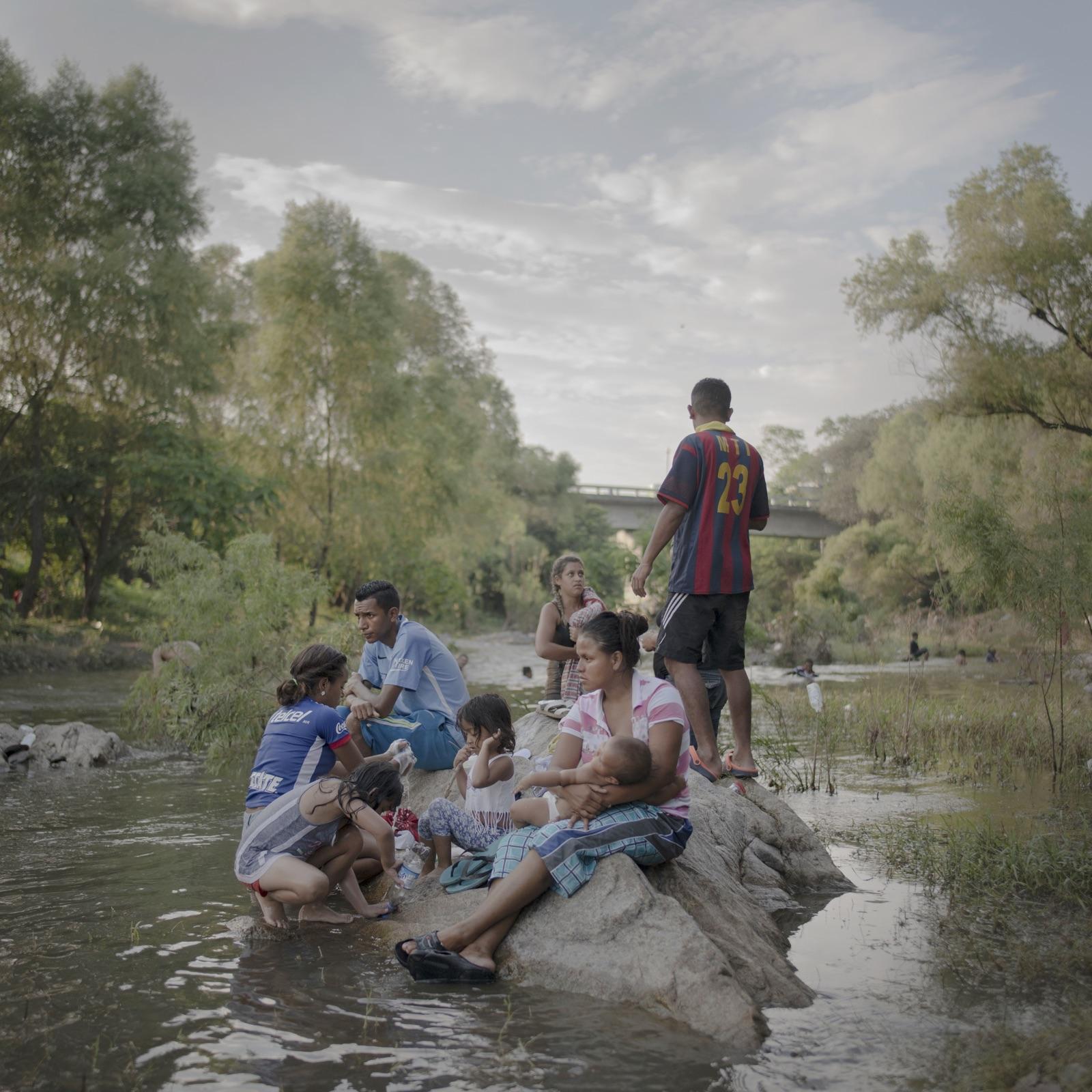 foto van vluchtende familie uit Midden-Amerika zittend op een rots die uitsteekt boven de rivier