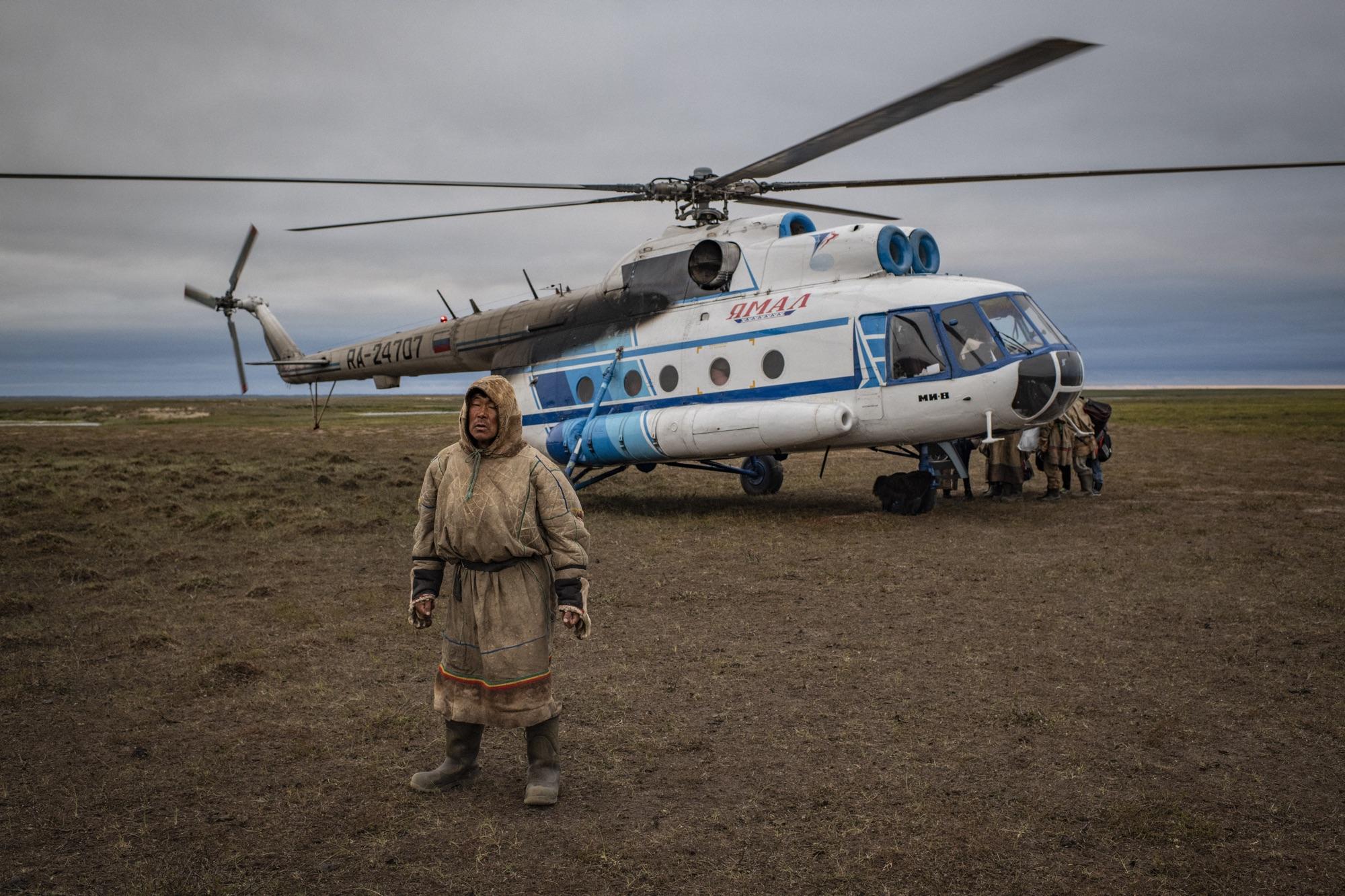Een man in een eskimopak staat op de noordpool waar geen ijs meer ligt met achter hem een vliegtuigje waar anderen spullen aan het uit- en inladen zijn