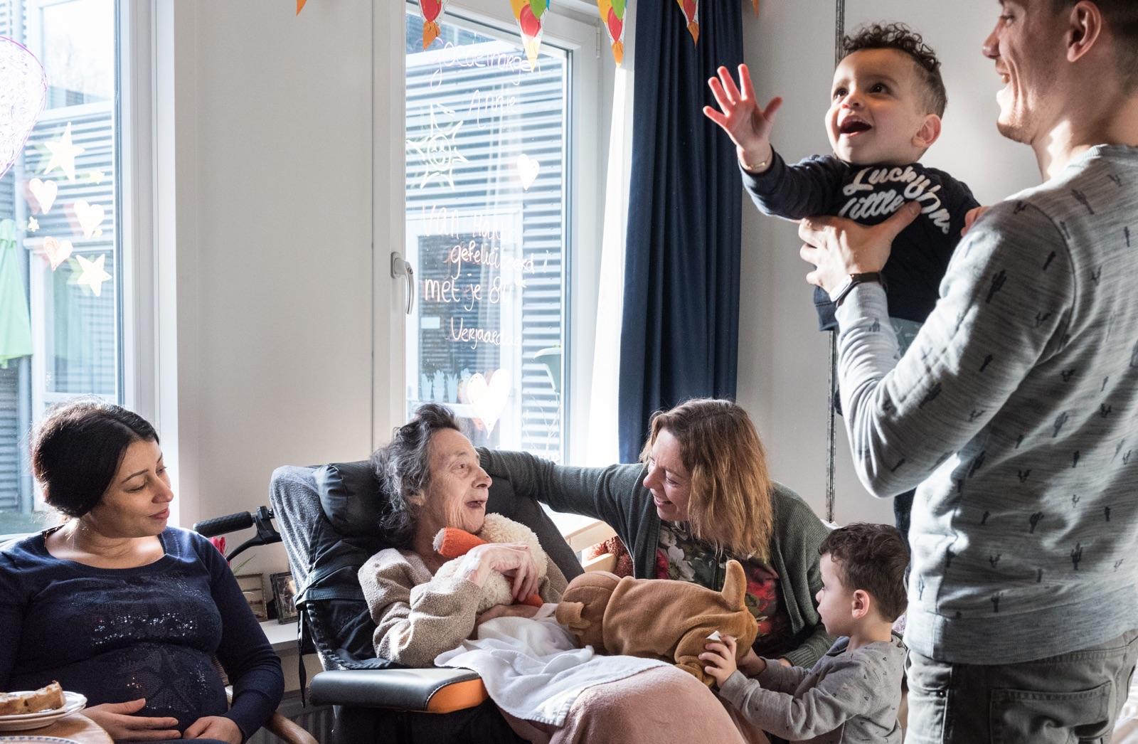 foto van oude vrouw in rolstoel met familie eromheen op haar verjaardag