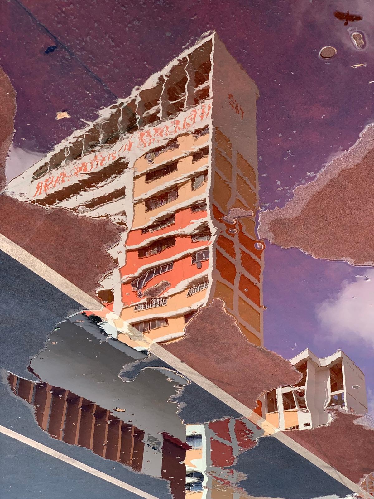 foto van een gebouw weerspiegeld in een plas water