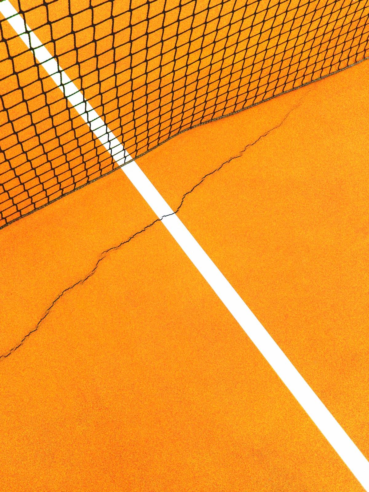 foto van een net van een tennisbaan met de baan eronder liggend waar een scheur in te zien is
