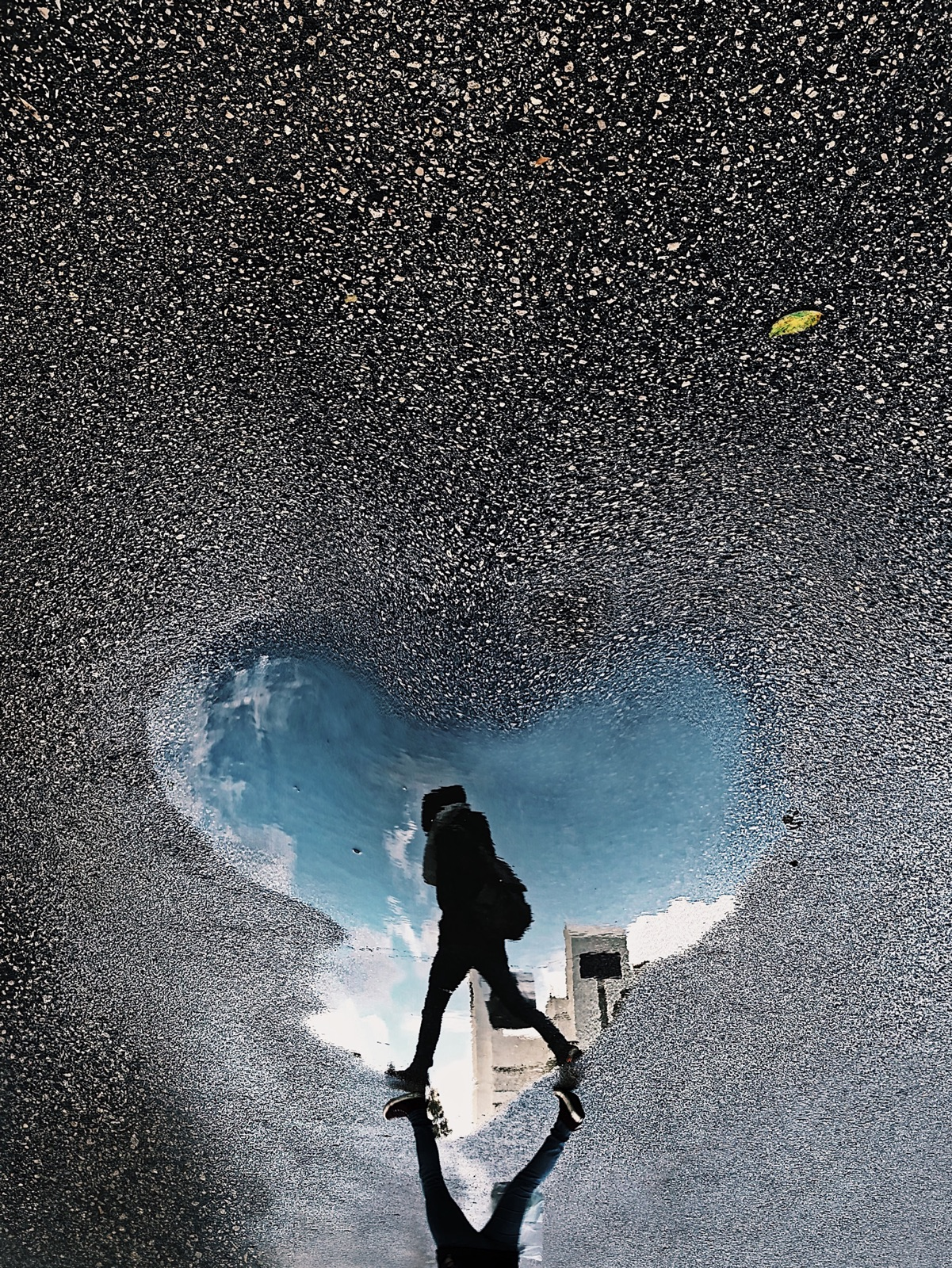 foto van een hartvormige plas op asfalt waarin je een persoon weerspiegeld ziet lopen