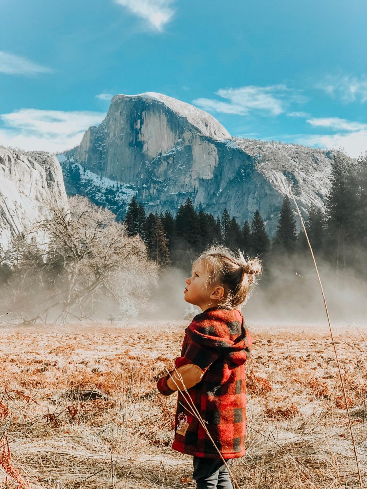 foto van een klein meisje met roodzwart geblokte winterjas die op omhoog kijkt en op de achtergrond een berg en bossen en blauwe lucht