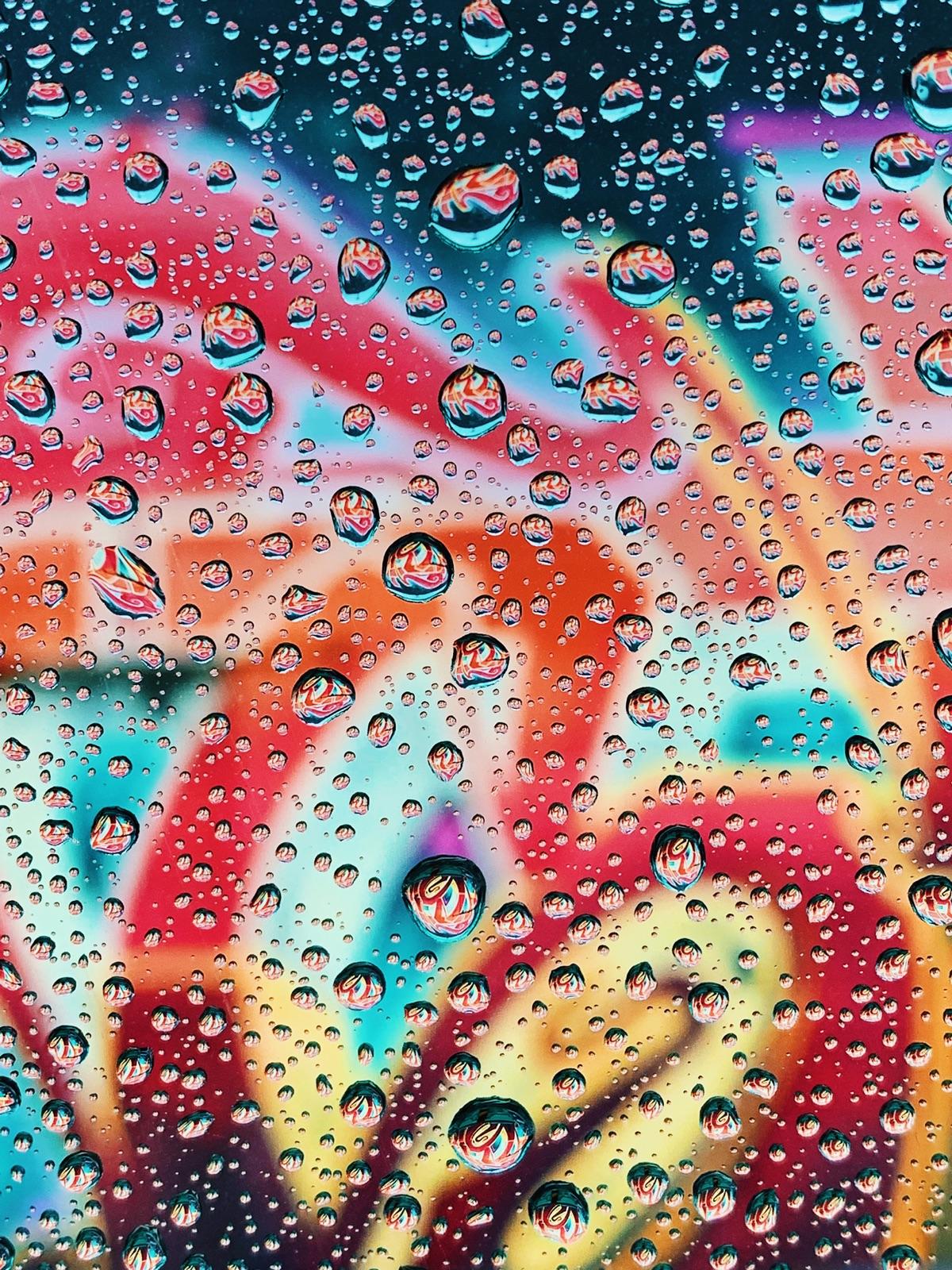 foto van waterdruppels op een ruit met allemaal kleuren erachter