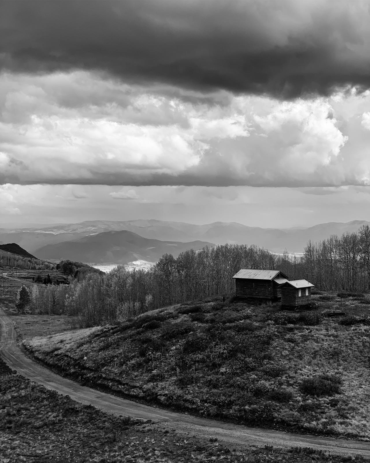 zwartwit foto van een berglandschap met heuvel, schuur en bomen en donkere wolkenlucht