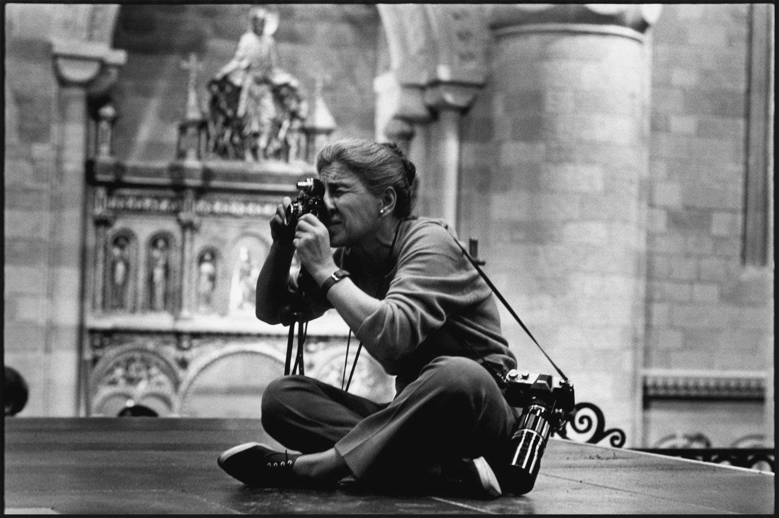 foto van Eve Arnold aan het fotograferen zittend op de grond