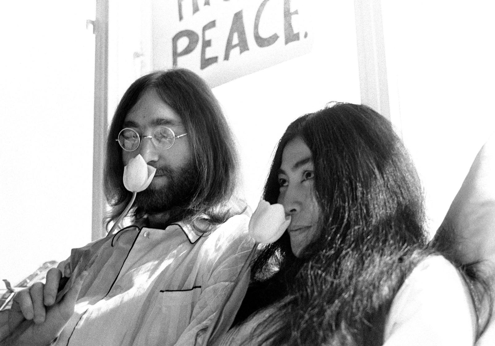 foto van John Lennon en zijn bruid Yoko Ono in bed in het Hilton Hotel ruikend aan een witte tulp