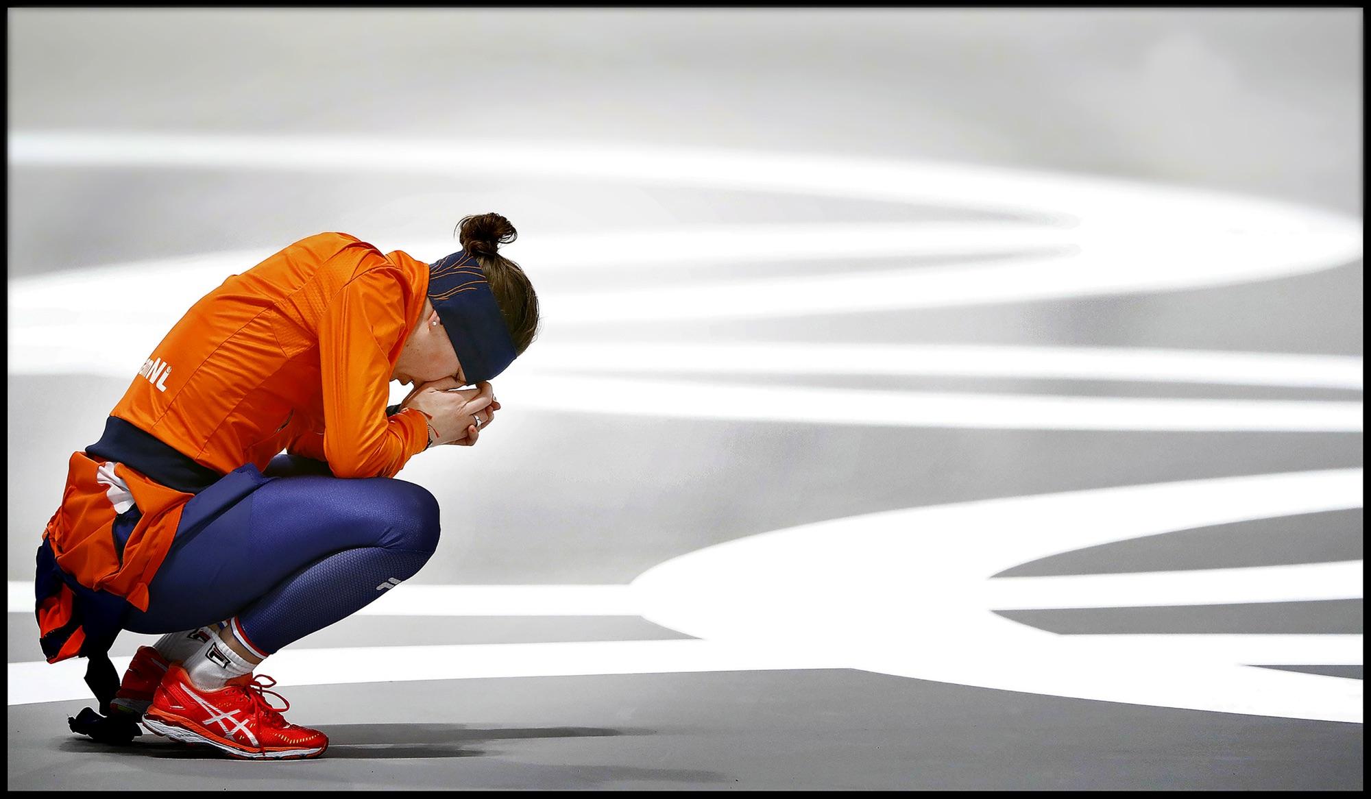 foto van een hardloopster met oranje shirt en blauwe broek op de olympische spelen die op haar hurken haar gezicht in haar handen verbergt