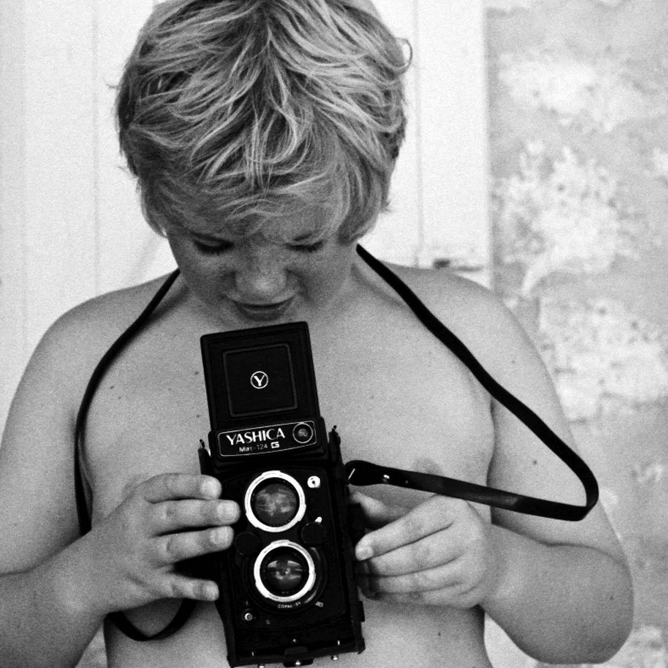 foto van een jongetje die in een analoge camera kijkt die hij voor zijn blote borst houdt