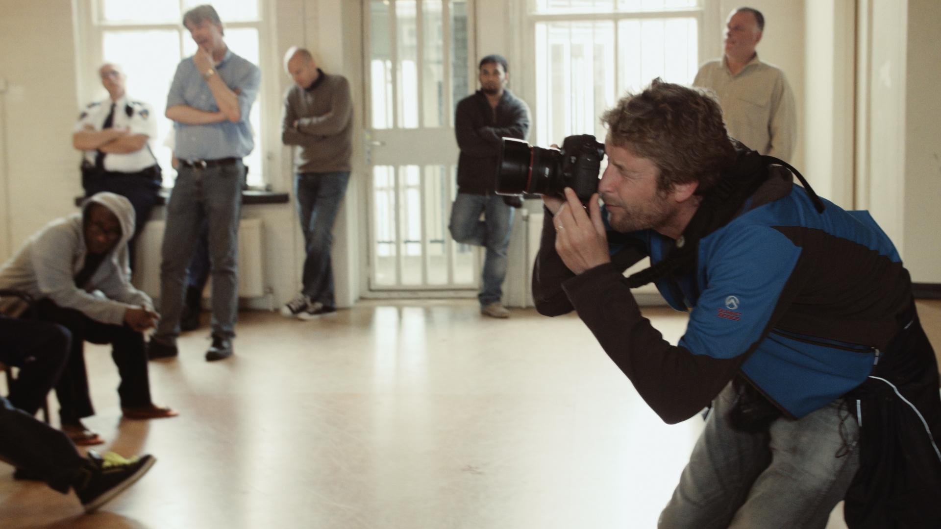 foto van een fotograaf met camera die een foto neemt in een ruimte waar ook andere mannen staan te wachten