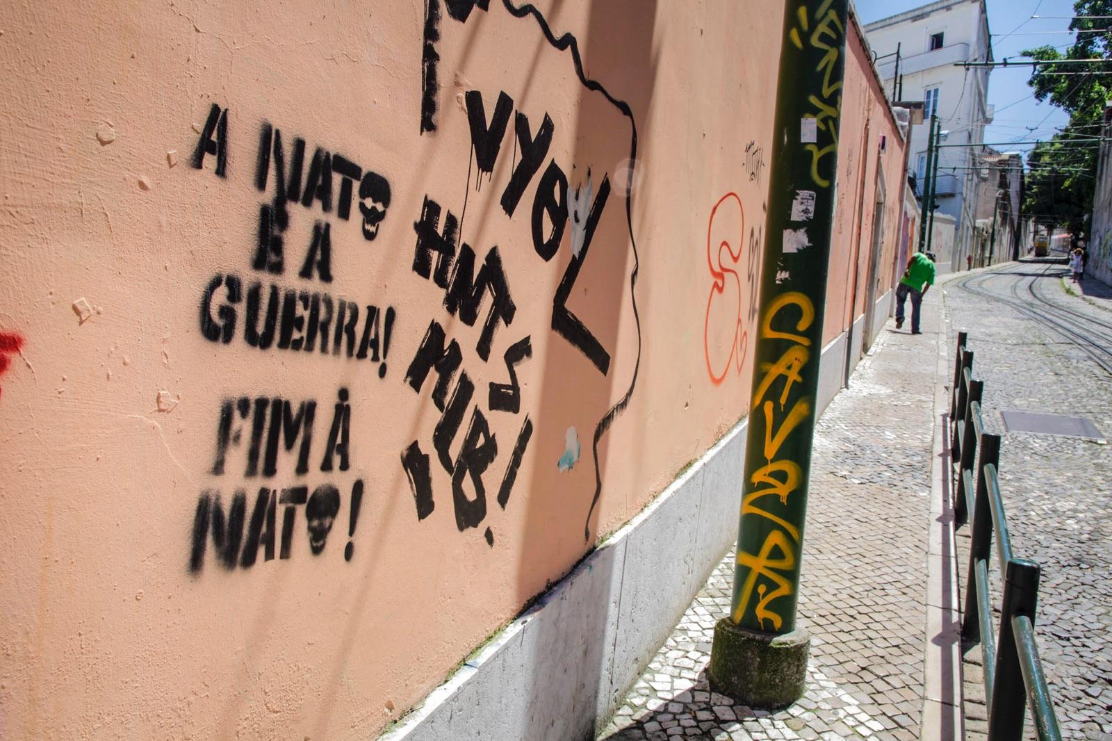 foto van een muur in Lissabon met graffiti en een stuk straat waar een man in een groen shirt kreupel loopt