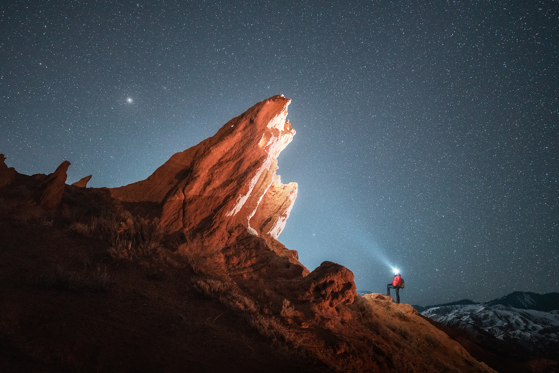 foto van de melkweg bij nacht boven een berg met een man met een licht op zijn hoofd die er op omhoog loopt