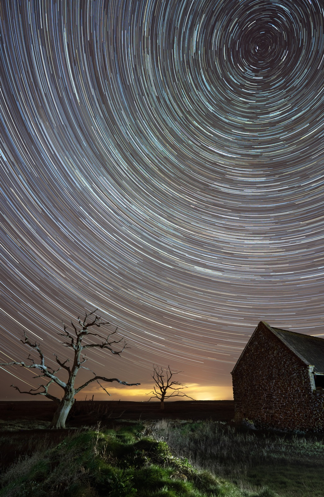 foto van een sterrenspoor bij nacht boven een weiland met een huis en twee kale bomen