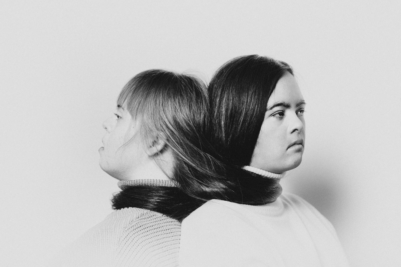 foto van twee vrouwen met down syndroom die met hun ruggen tegen elkaar aan zitten en hun haar om elkaar heen hebben