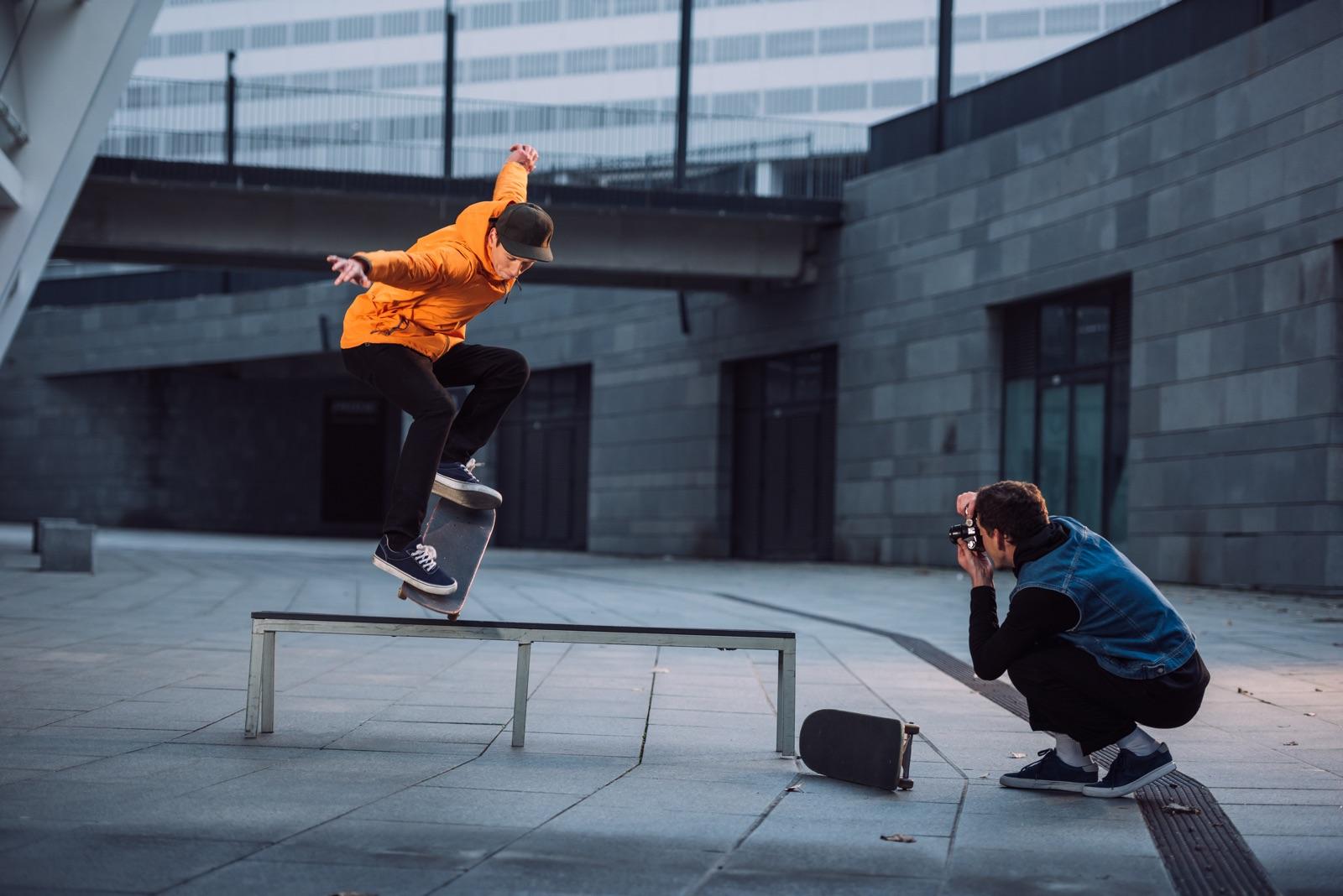 foto van een fotograaf die een skater fotografeert die met zijn plank op een bankje balanceert