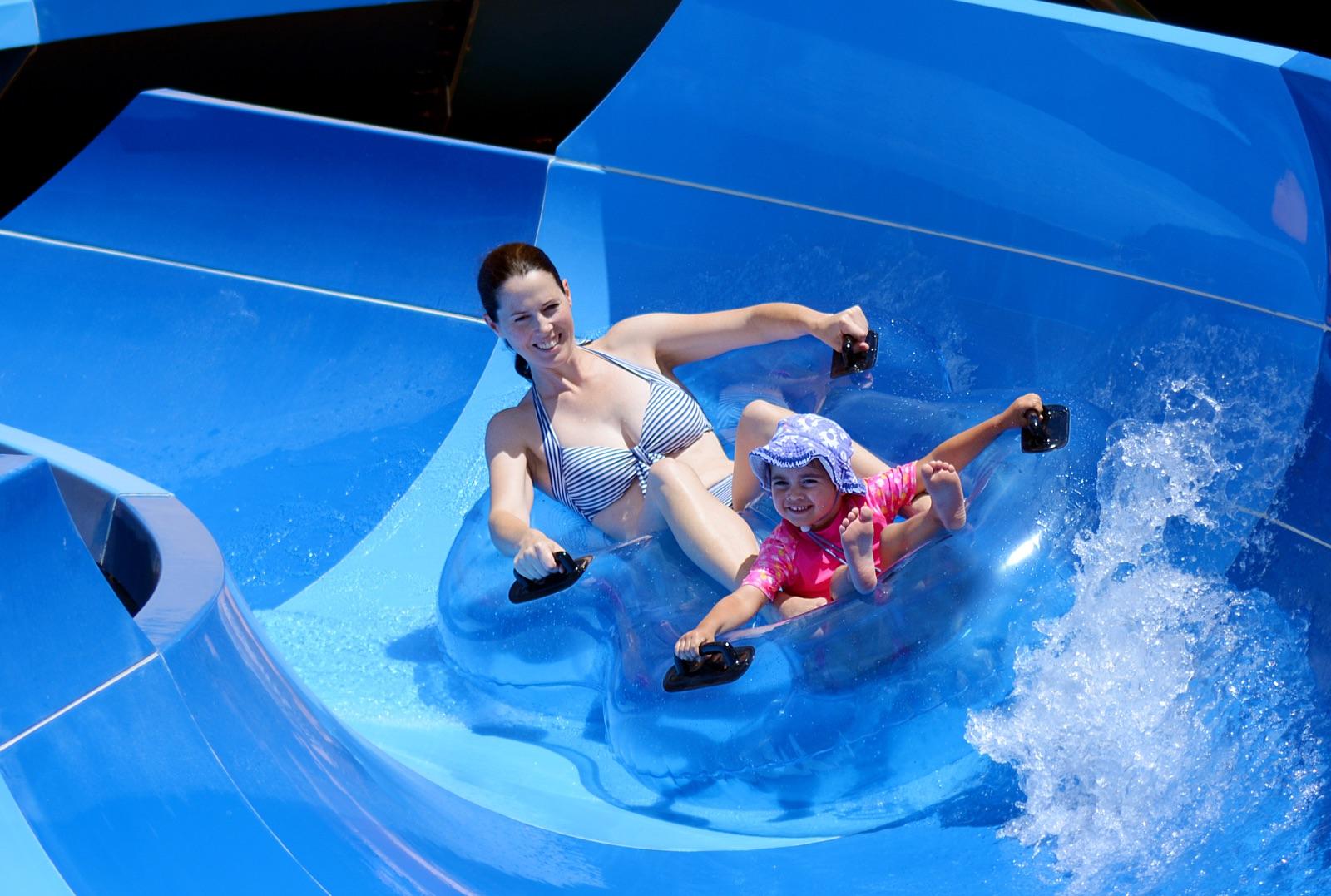 foto van moeder en zoon tje die van een waterglijbaan afkomen