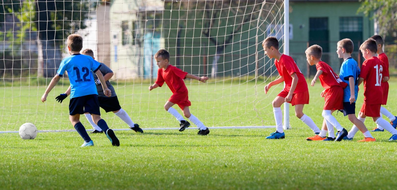 foto van een jong voetbalteam in actie bij doel