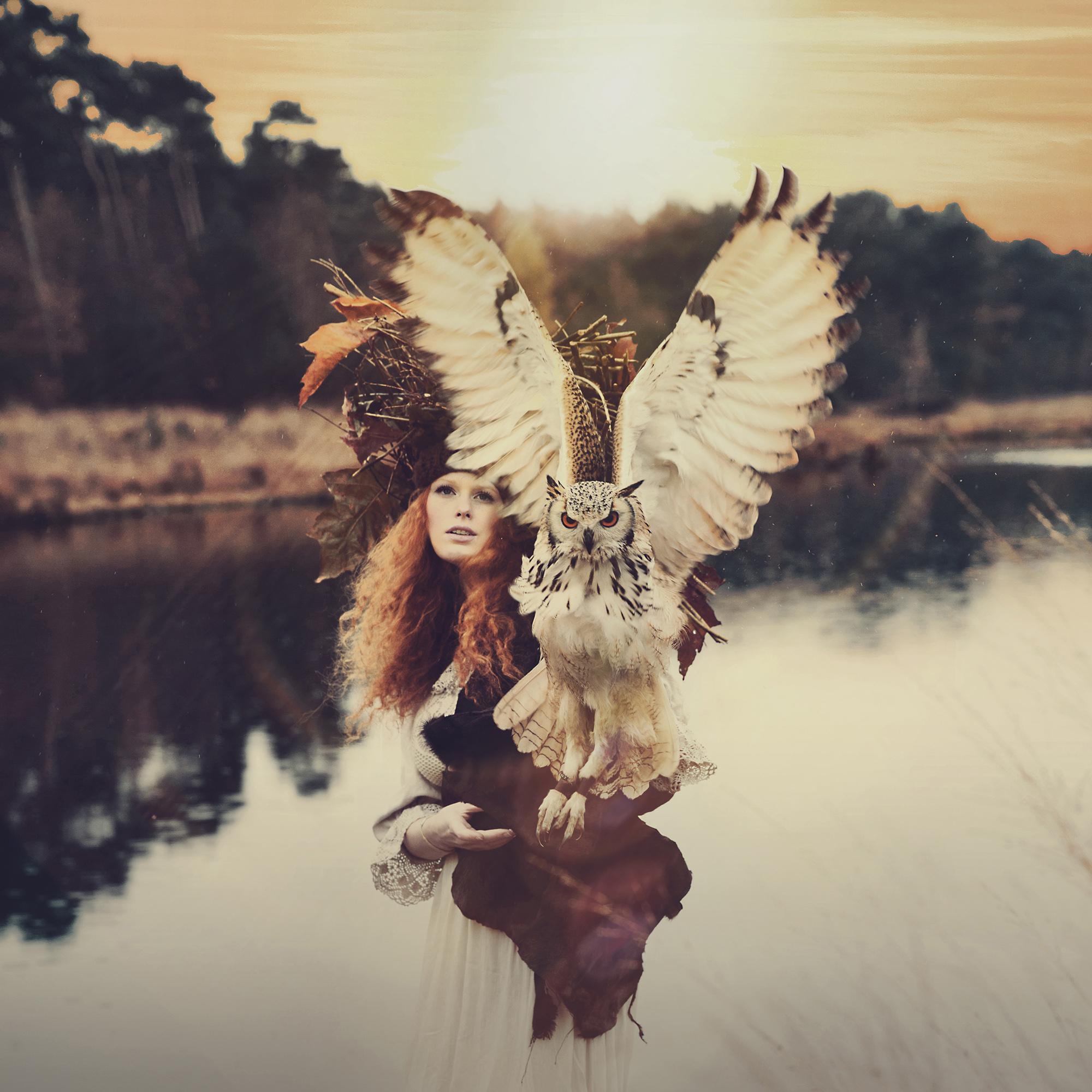 foto van vrouw met grote uil met achtergrond water en bos van Lione Bakker