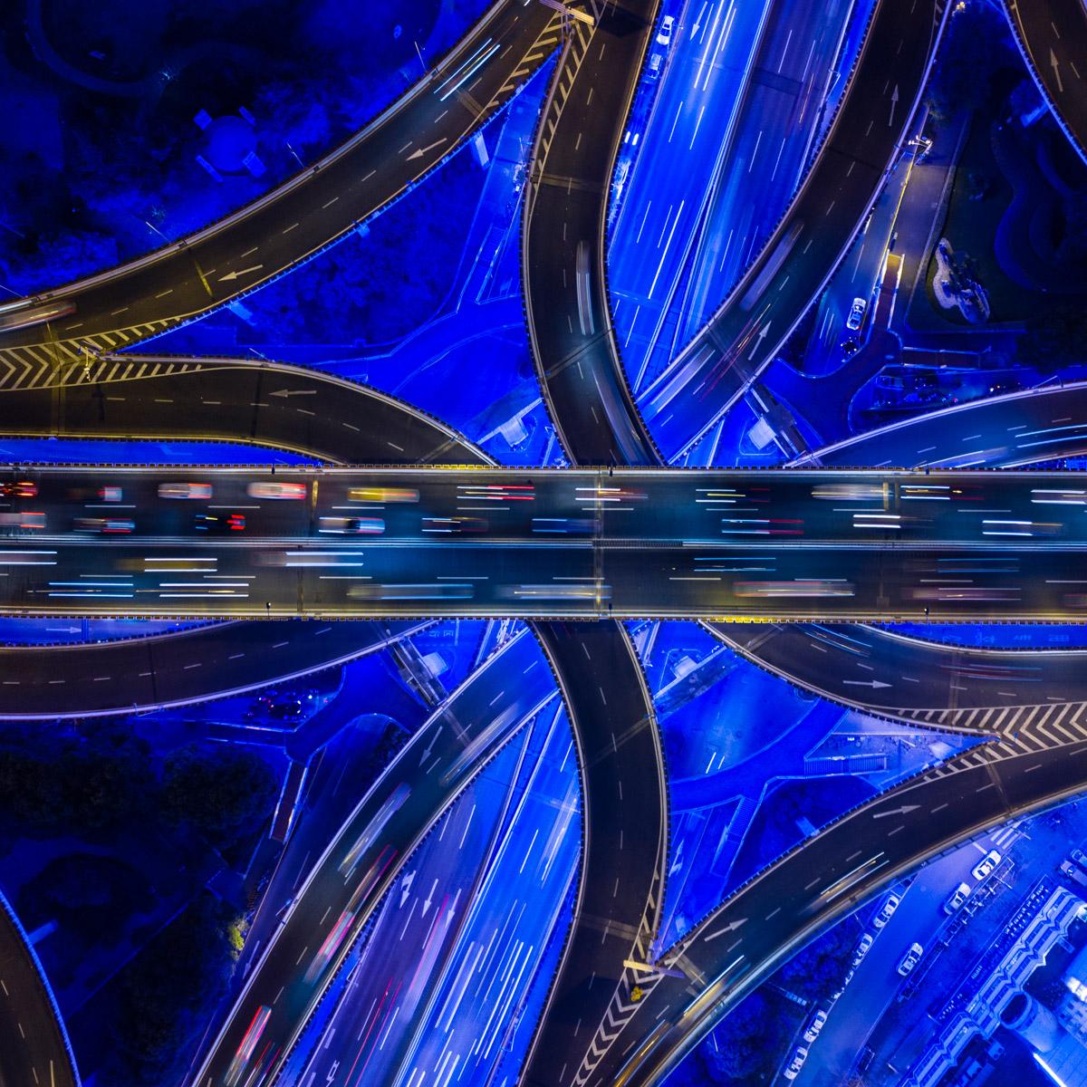 foto van bovenaf van een netwerk van snelwegen die over elkaar heen lopen in blauw