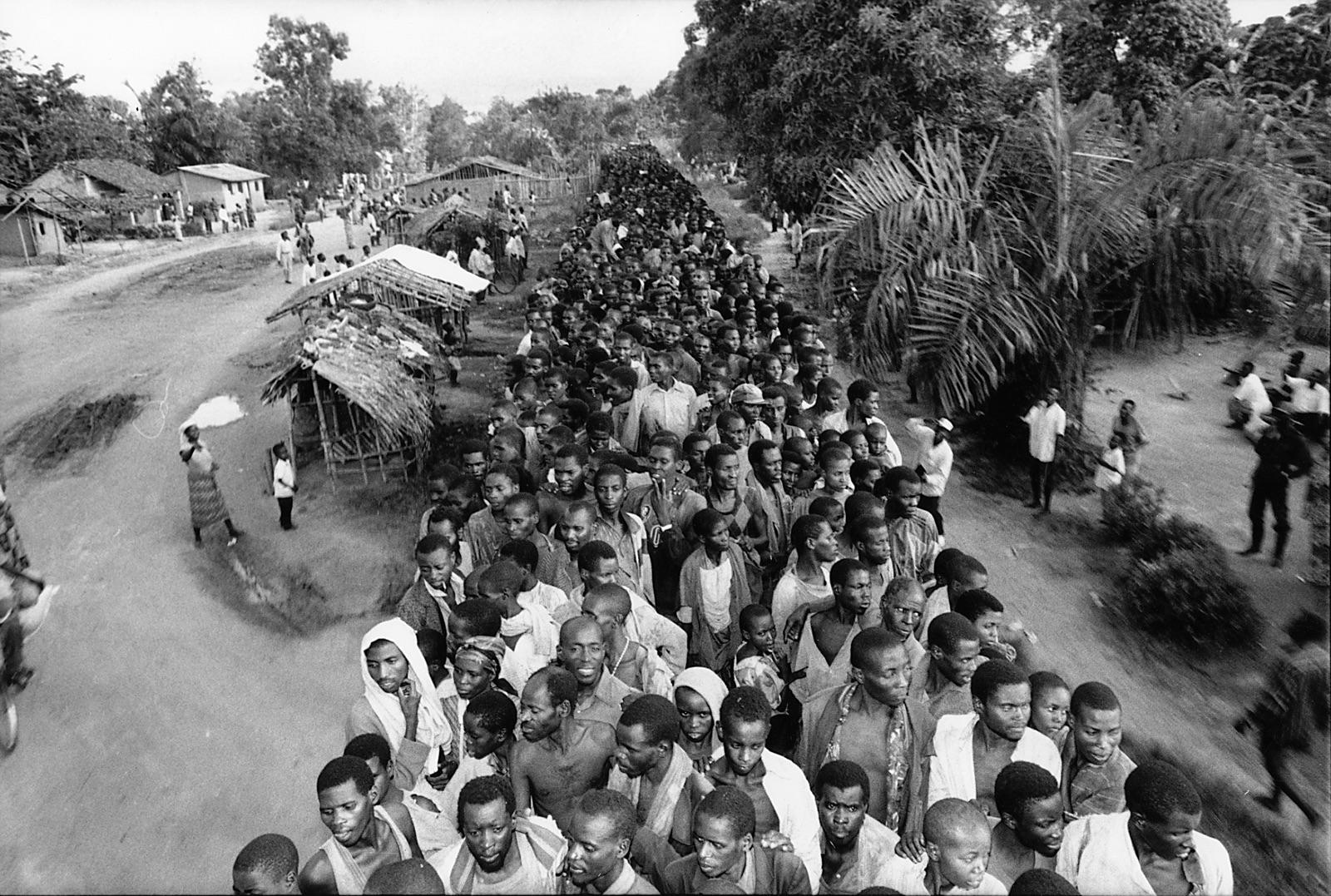 foto van een rij arbeiders in Rwanda in een bos met hutten