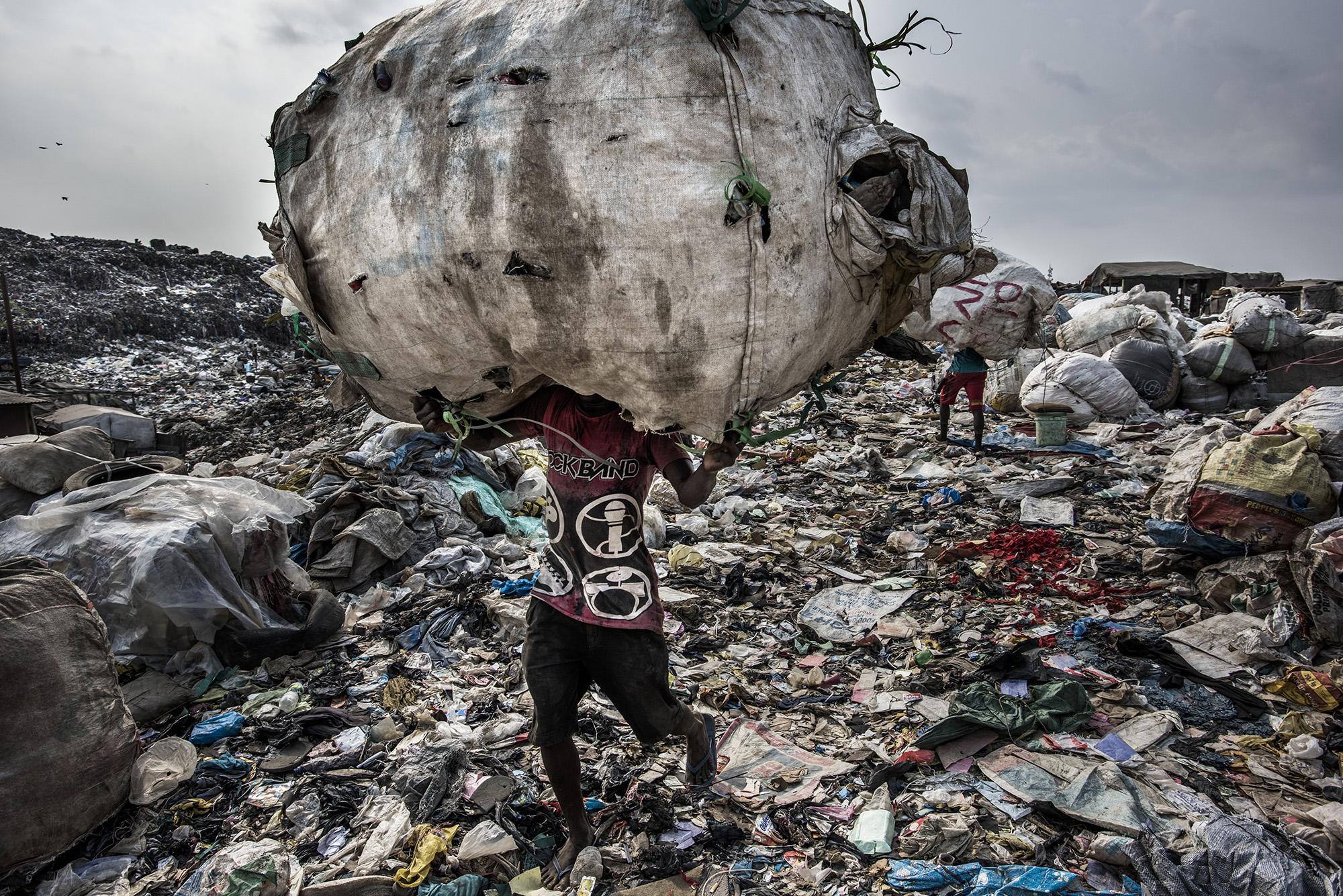 foto van Kadir van Lohuizen van een man met een zak met afval op zijn rug op een vuilnisbelt