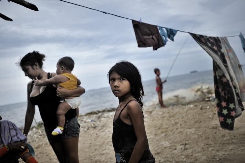 foto van Kadir van Lohuizen van een migrantenmoeder met een baby op de arm en een dochtertje en de zee op de achtergrond en was aan een lijn