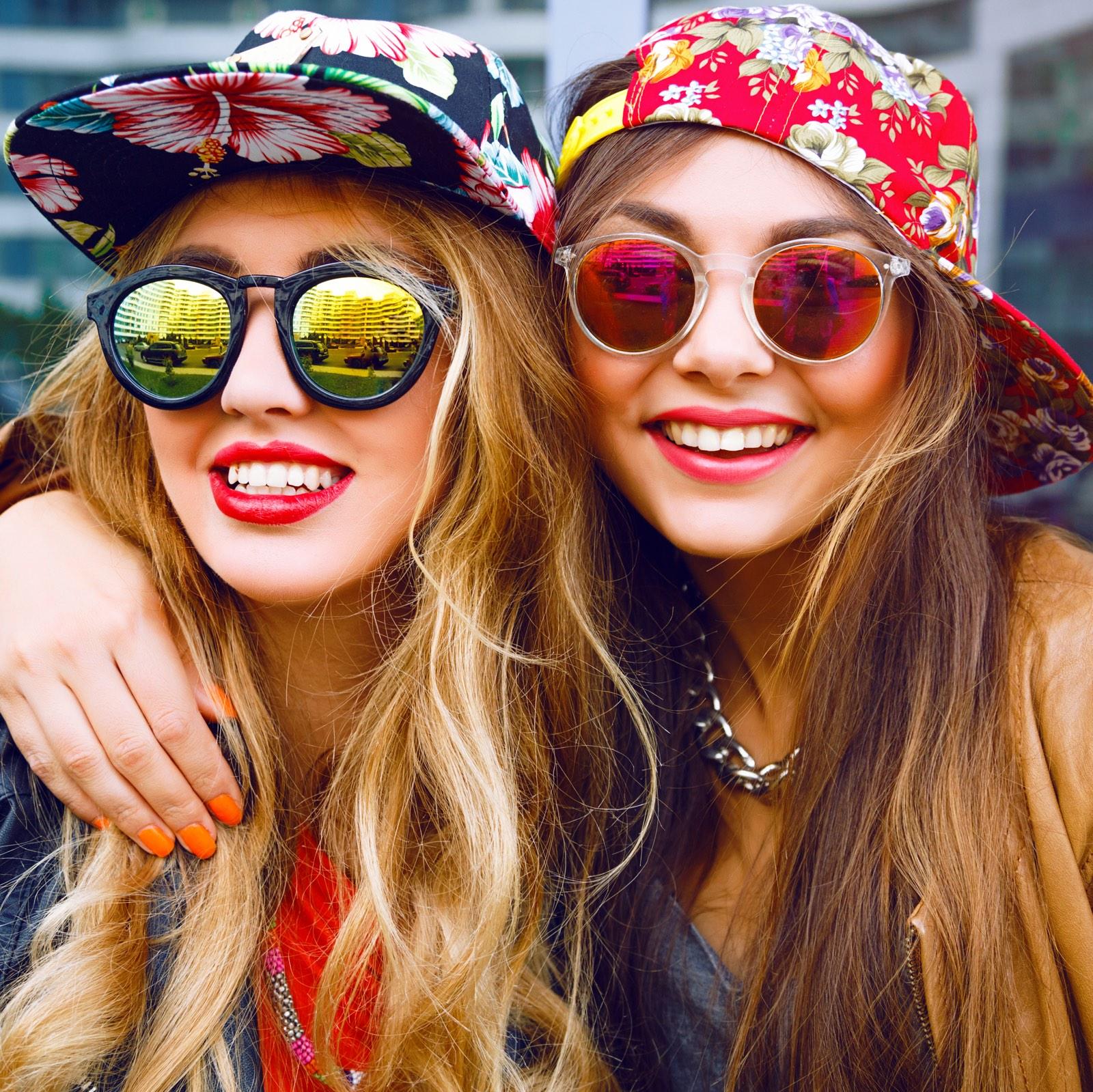 twee meisjes me zonnebrillen en hoedjes