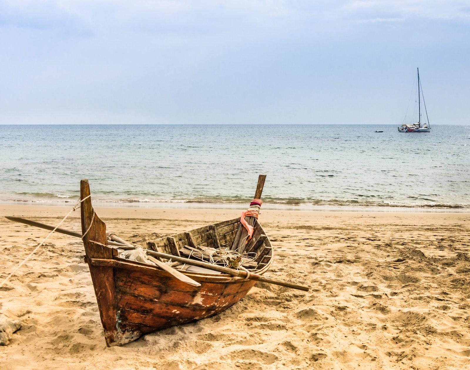 roeiboot op strand en op zee een zeilboot