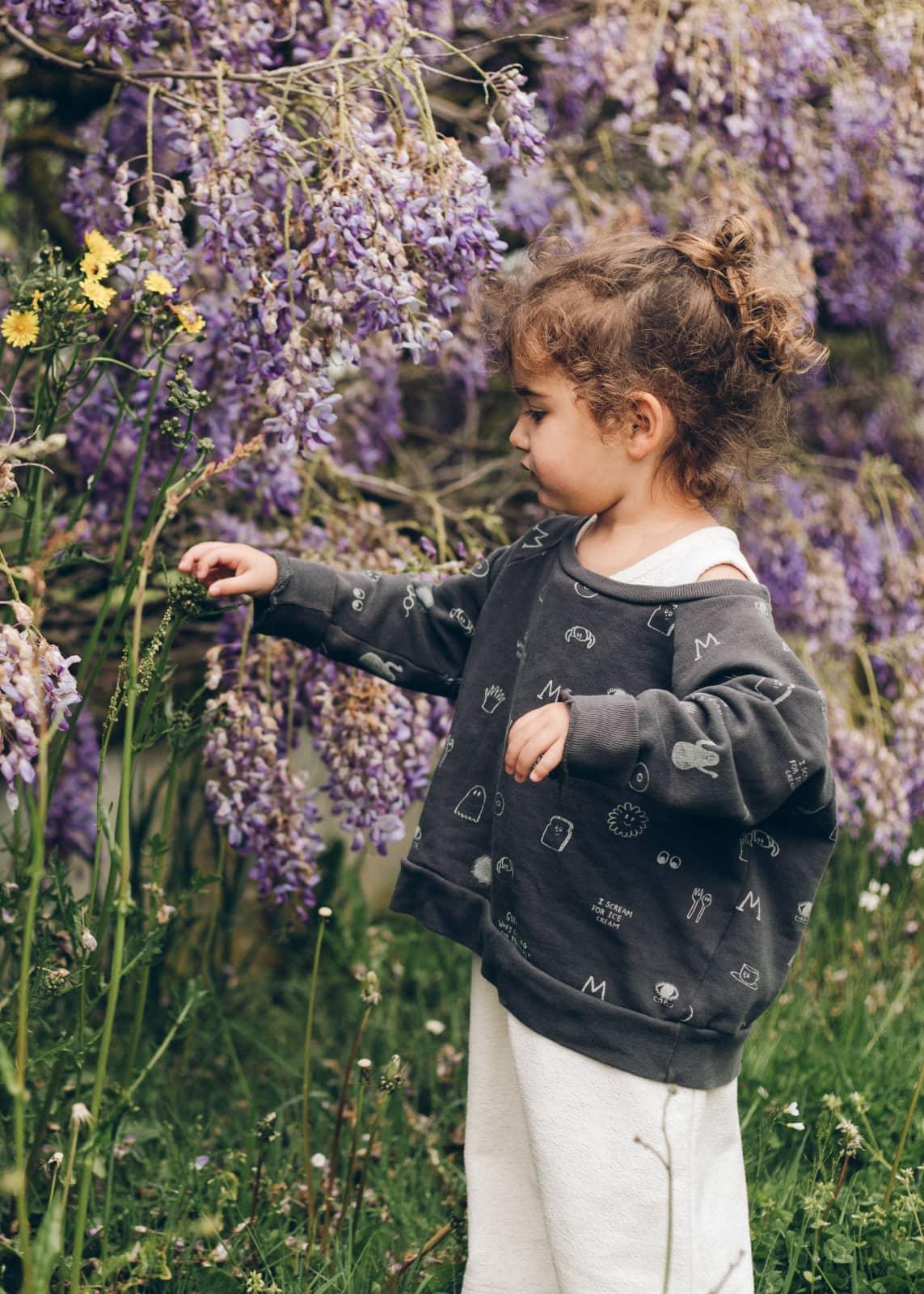 Klein meisje in tuin bij blauwe regen door Hannah Harding