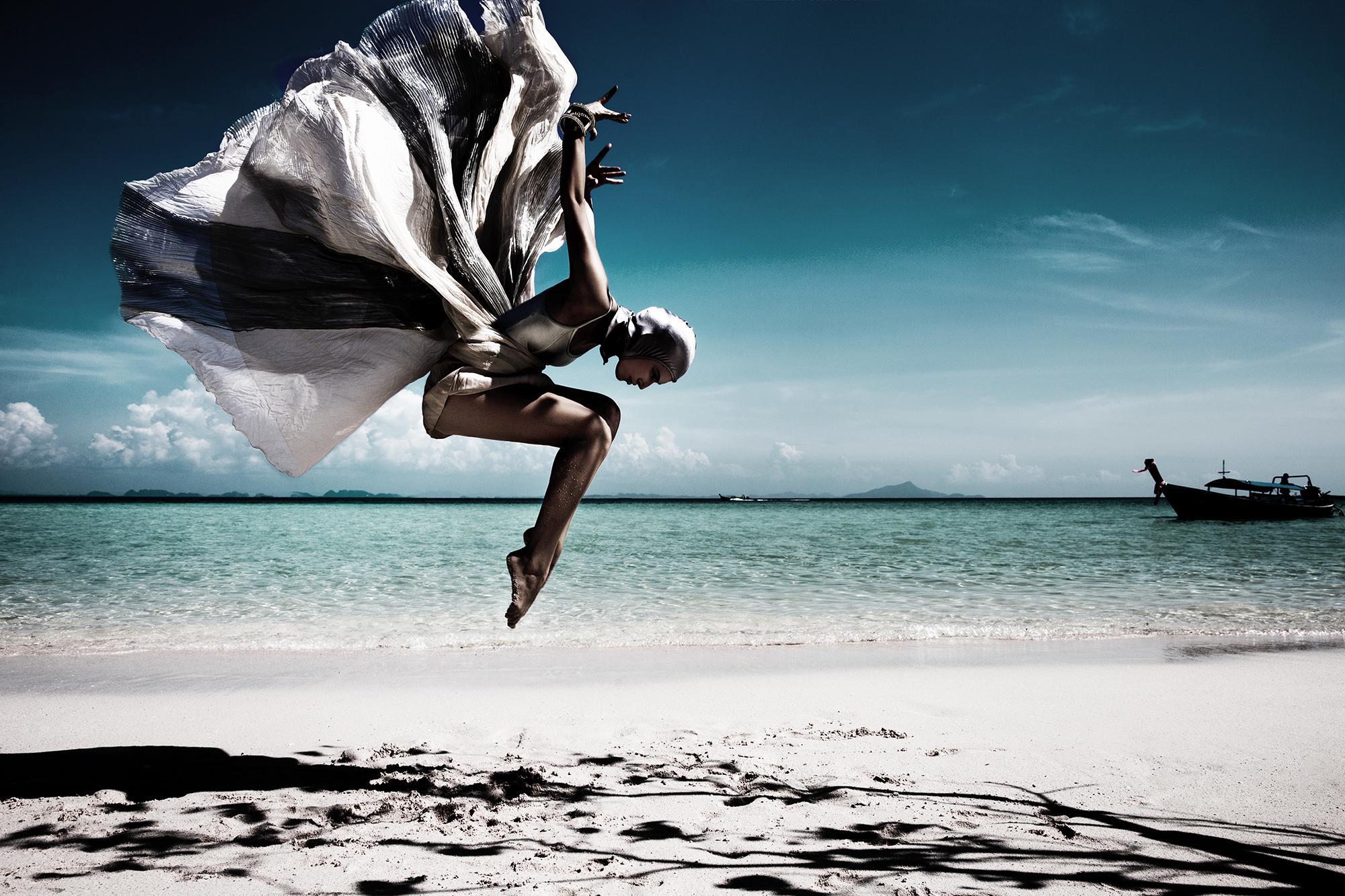 Modefotografie van vrouw met rok als vleugels springend op caribisch strand door fotograaf Saurabh Dua