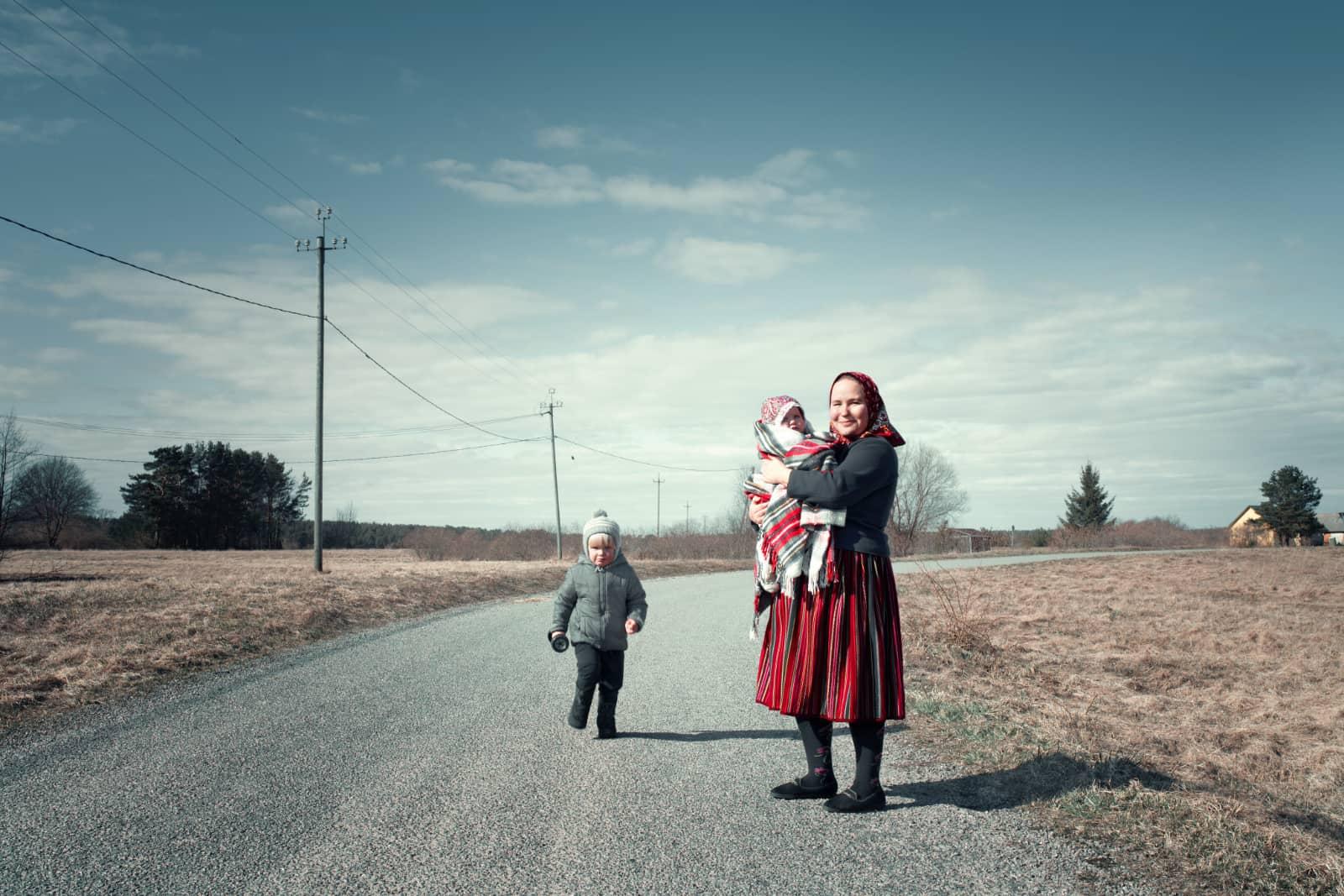 vrouw met kind op arm en kind ernaast op een weg in Kinhu Estland