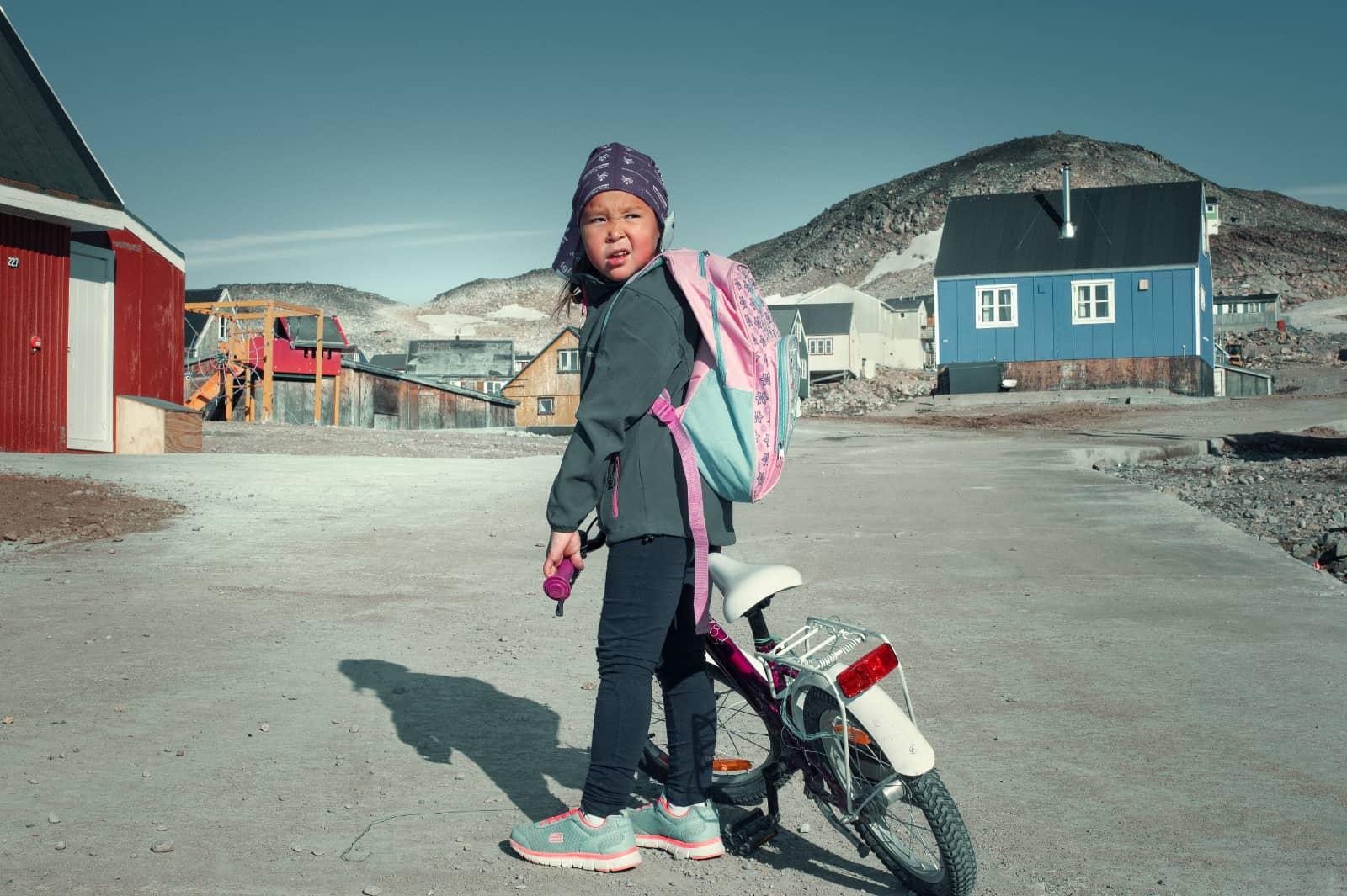 jongen met fiets in Groenland met rode en blauwe huizen tegen bergen achter hem