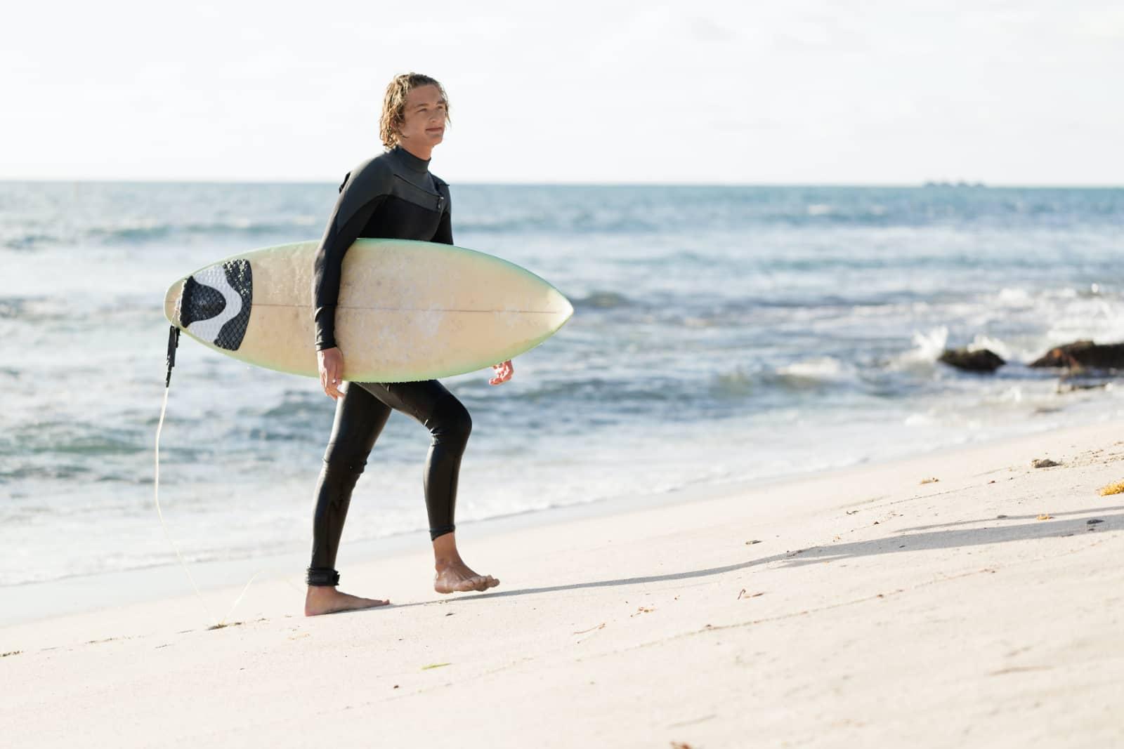 jonge man met surfplank bij de zee