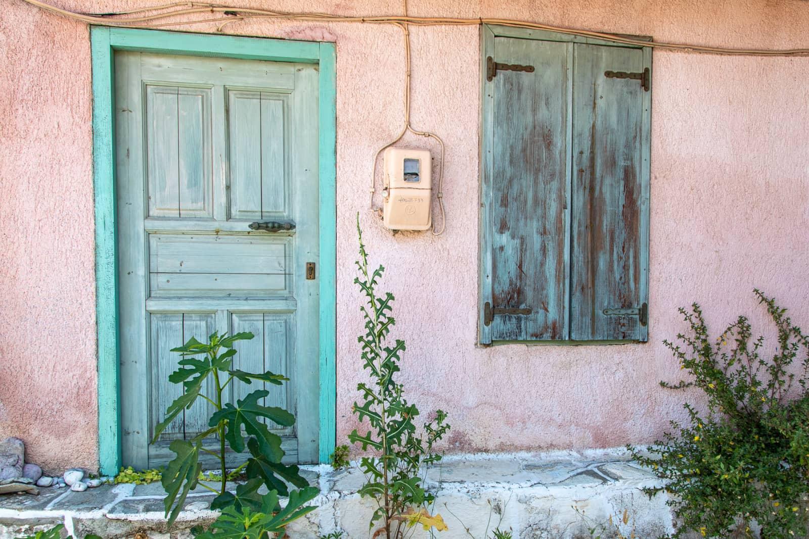 deur en raam in roze muur in Skopeloos, Griekenland